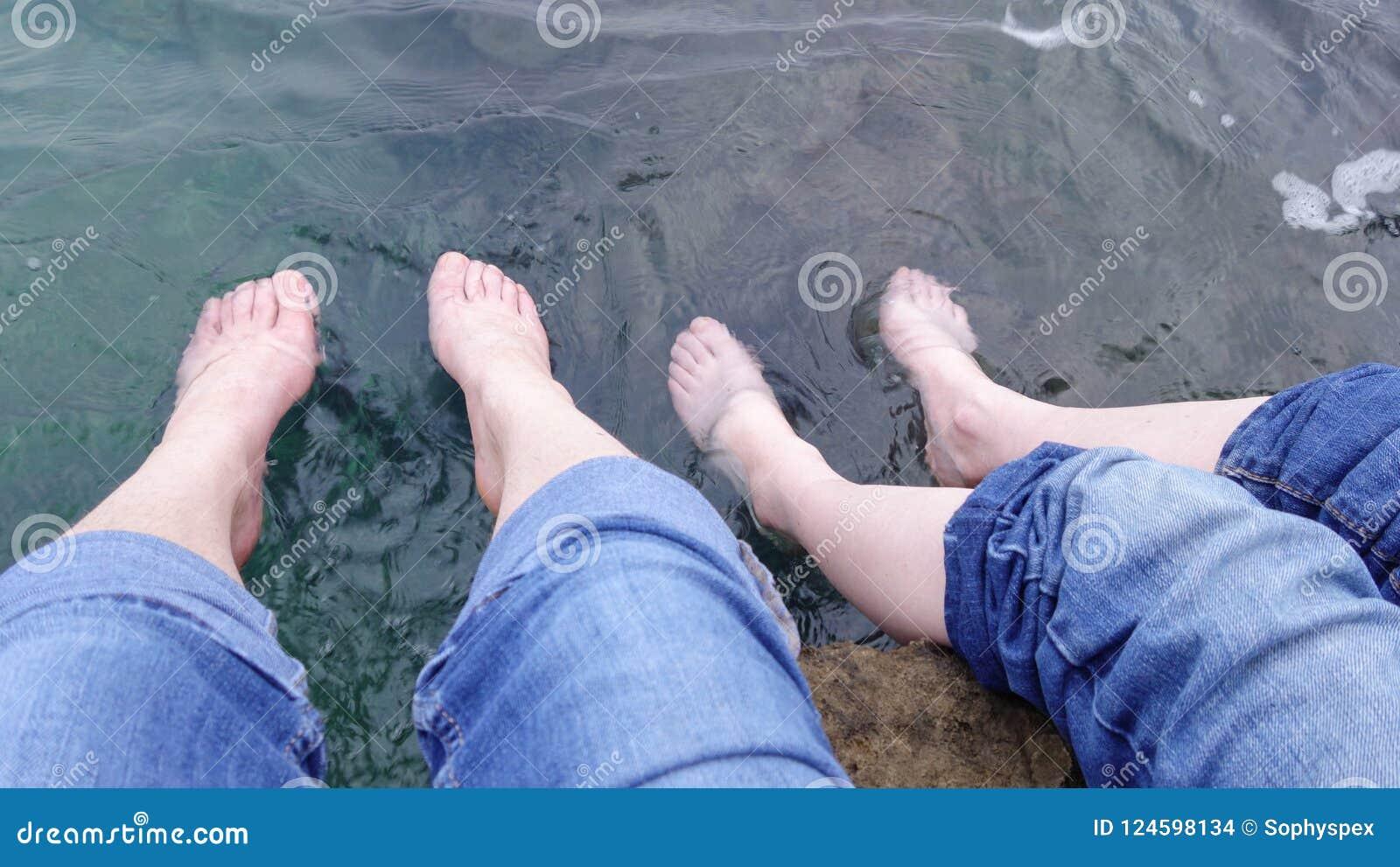 Two sets of feet paddling in the sea, Croatia