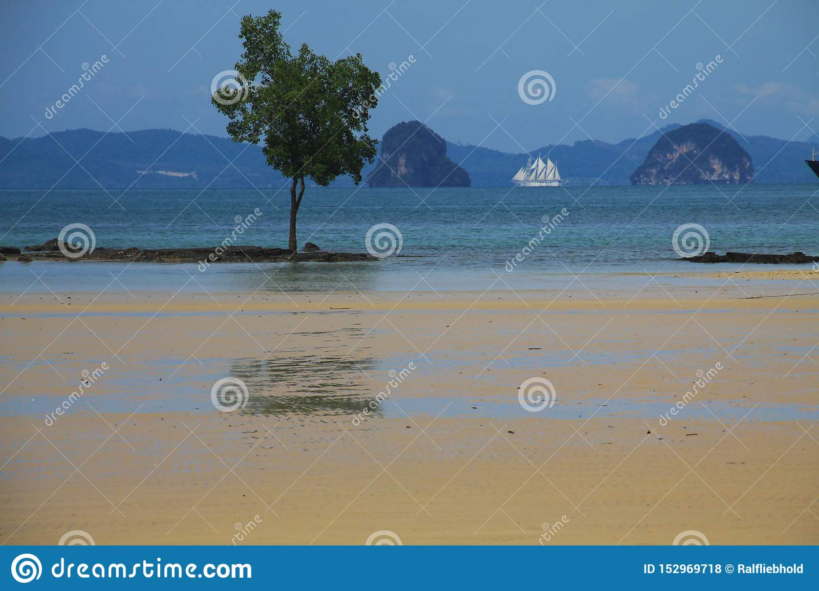 Low tide at Thailands coastline with rock formation, tree and sailing ship in the background, Ao Nang, Krabi