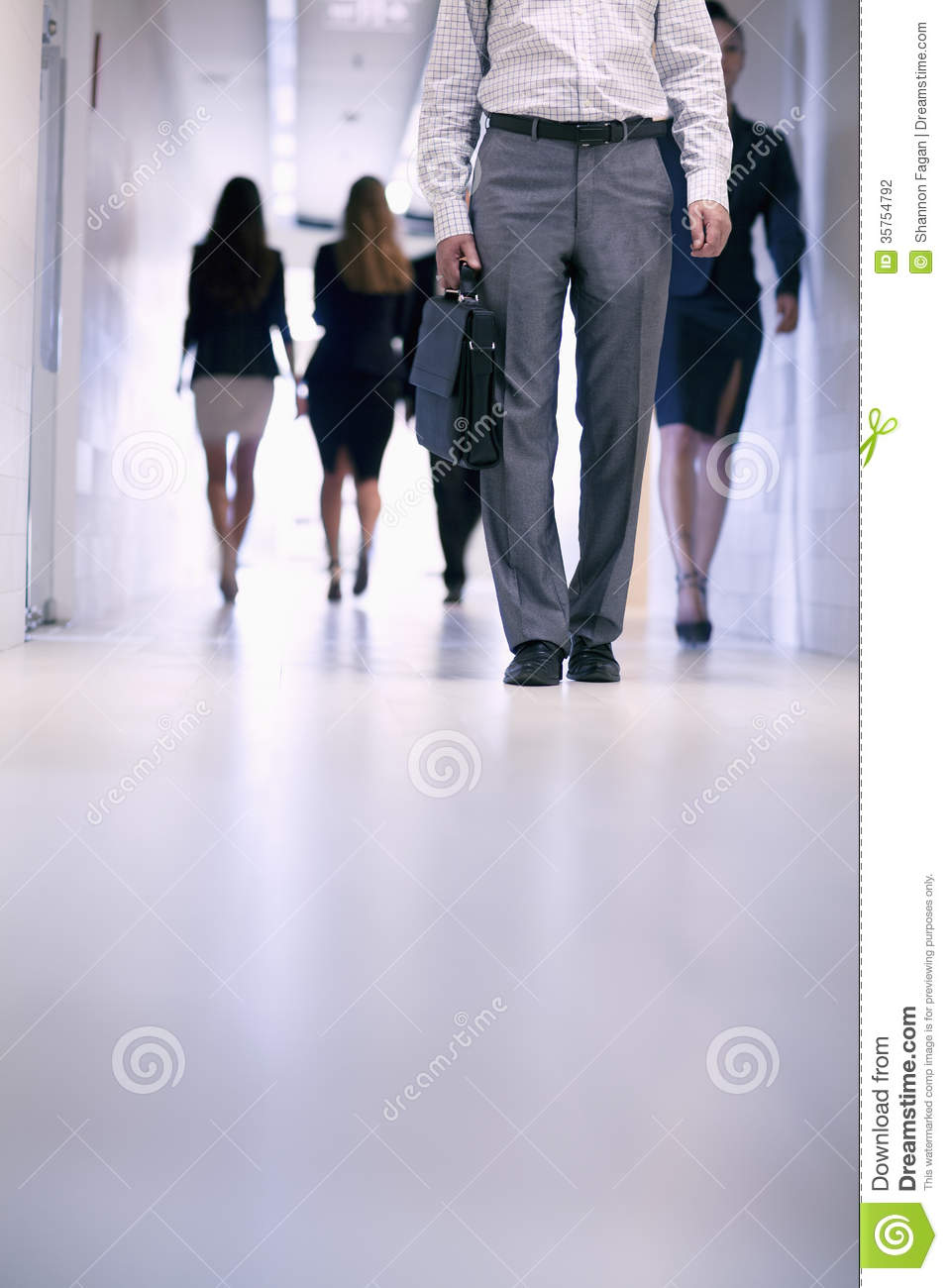 Low View Of People Walking Down The Corridor In An Office