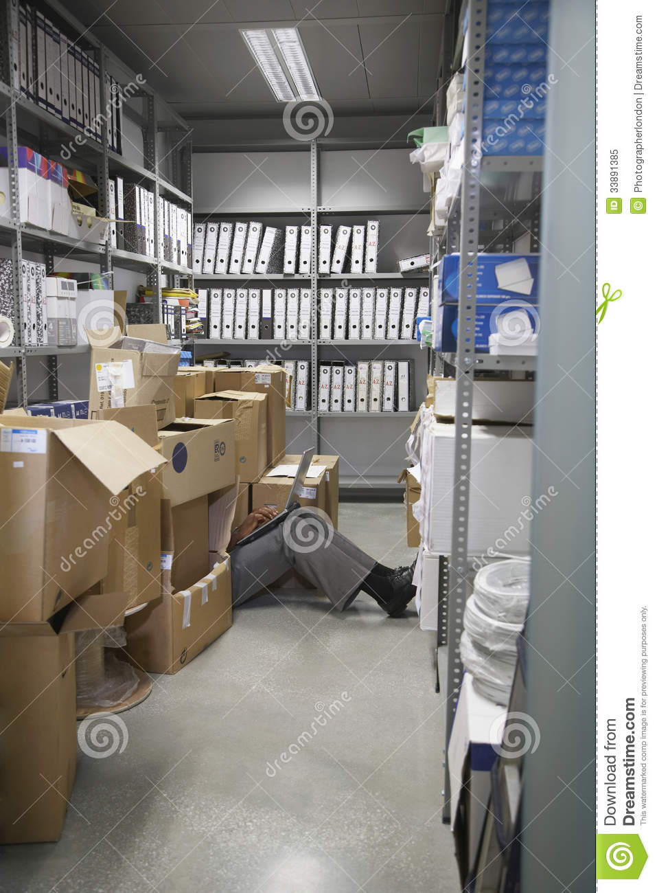 Lowsection Of Man With Laptop On Floor In Storage Room