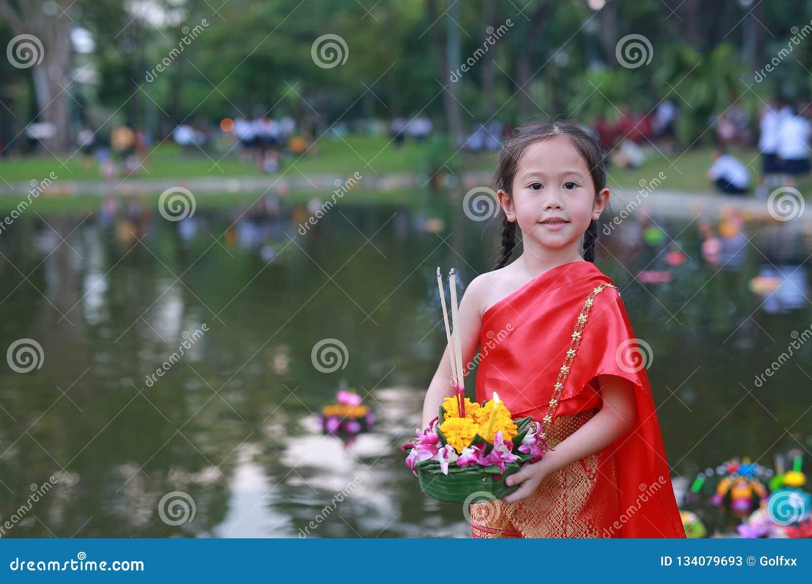 Loy Krathong-festival, Aziatisch Kindmeisje in Thaise traditionele kleding met holding krathong voor vergiffenisgodin Ganges aan