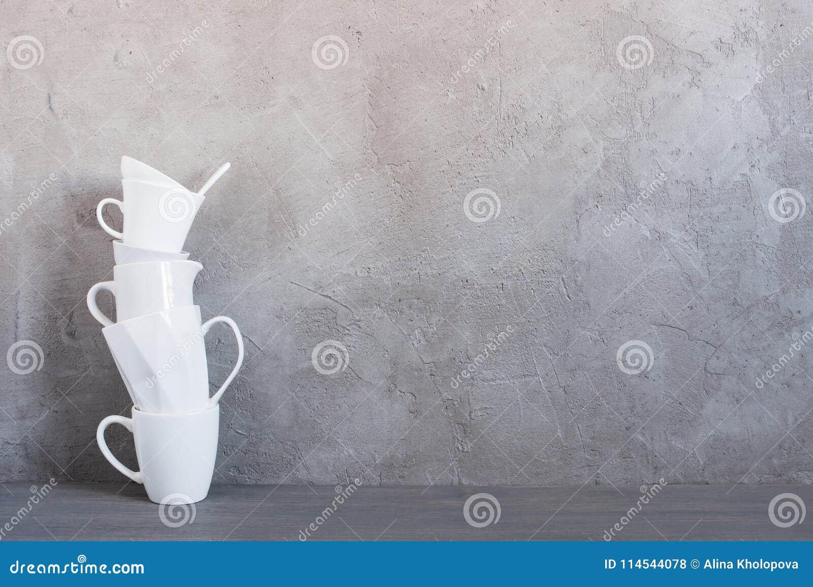 Loza blanca en la tabla contra la pared gris texturizada