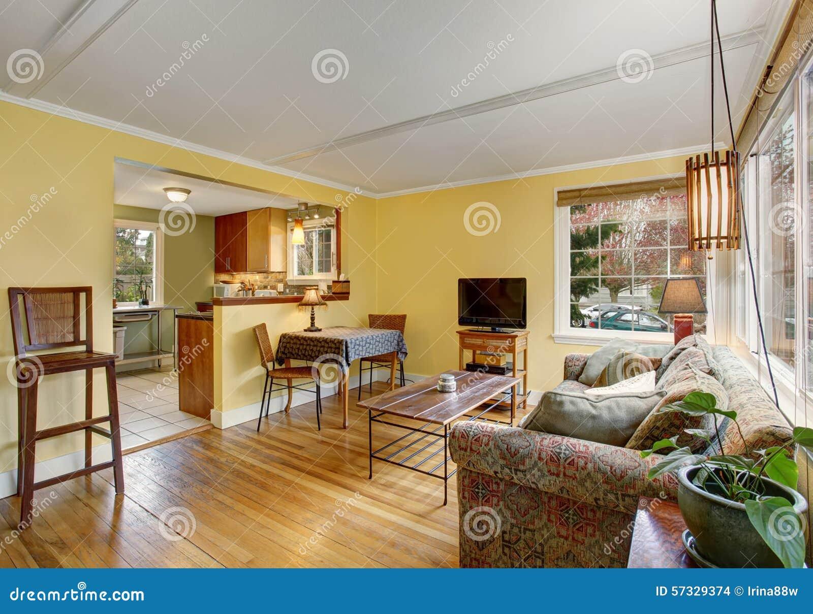 Älskvärd ädelträvardagsrum med den färgrika soffan och gula väggar ...
