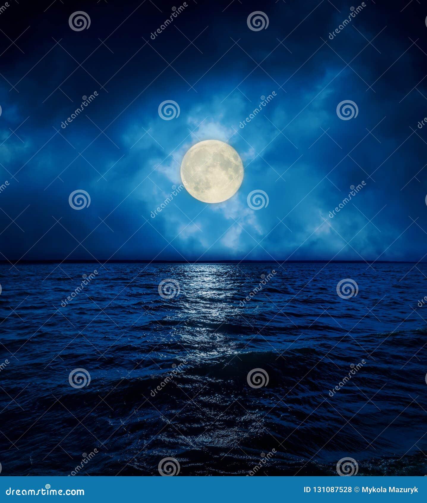 Lua cheia em nuvens dramáticas sobre a água escura