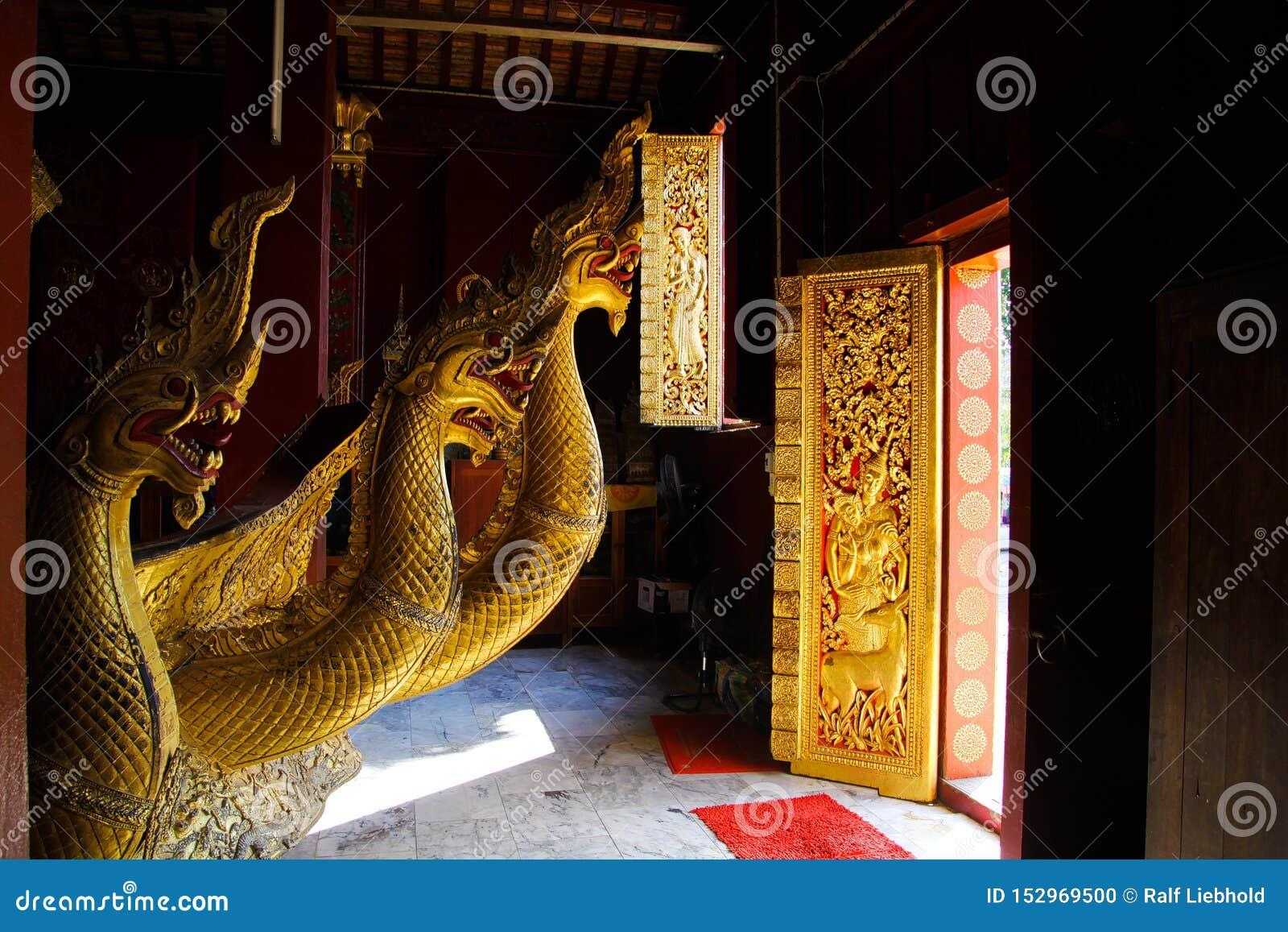 LUANG PRABANG WAT XIENG THONG, LAOS - DECEMBER 17. 2017: Dragon statues inside temple illuminated by natural sunlight