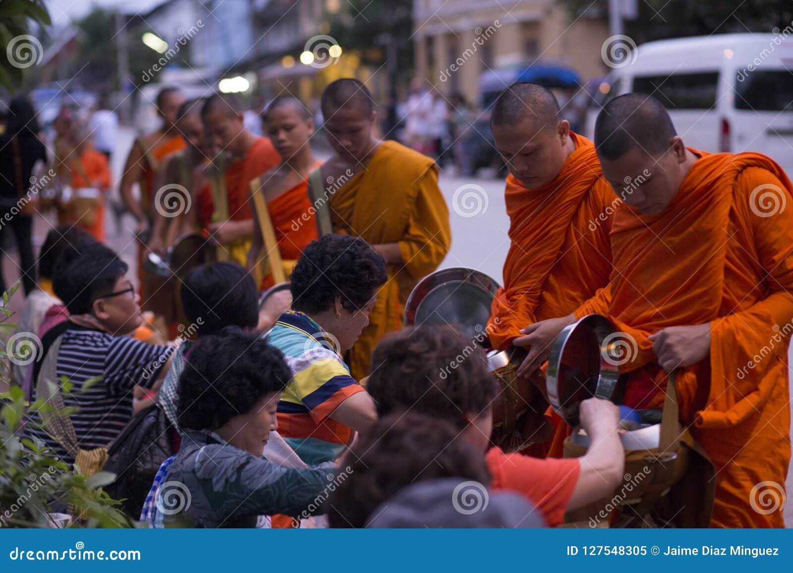 Luang Prabang, il Laos, monaci e la gente nelle elemosine che danno ceremon