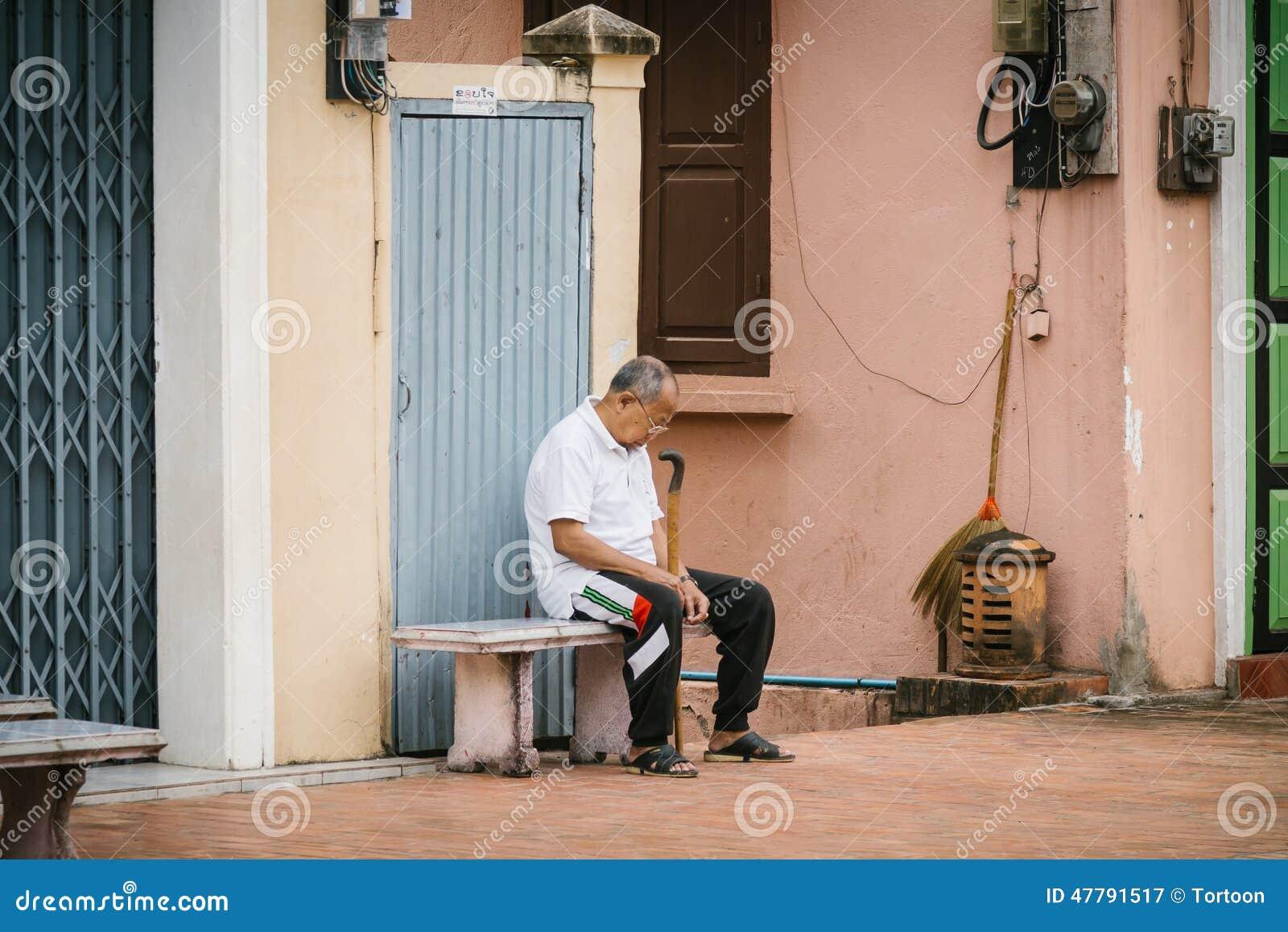 LUANG PRABANG LAOS, PAŹDZIERNIK, - 26; Niezidentyfikowany mężczyzna dosypianie na ulicie na Październiku 26, 2014