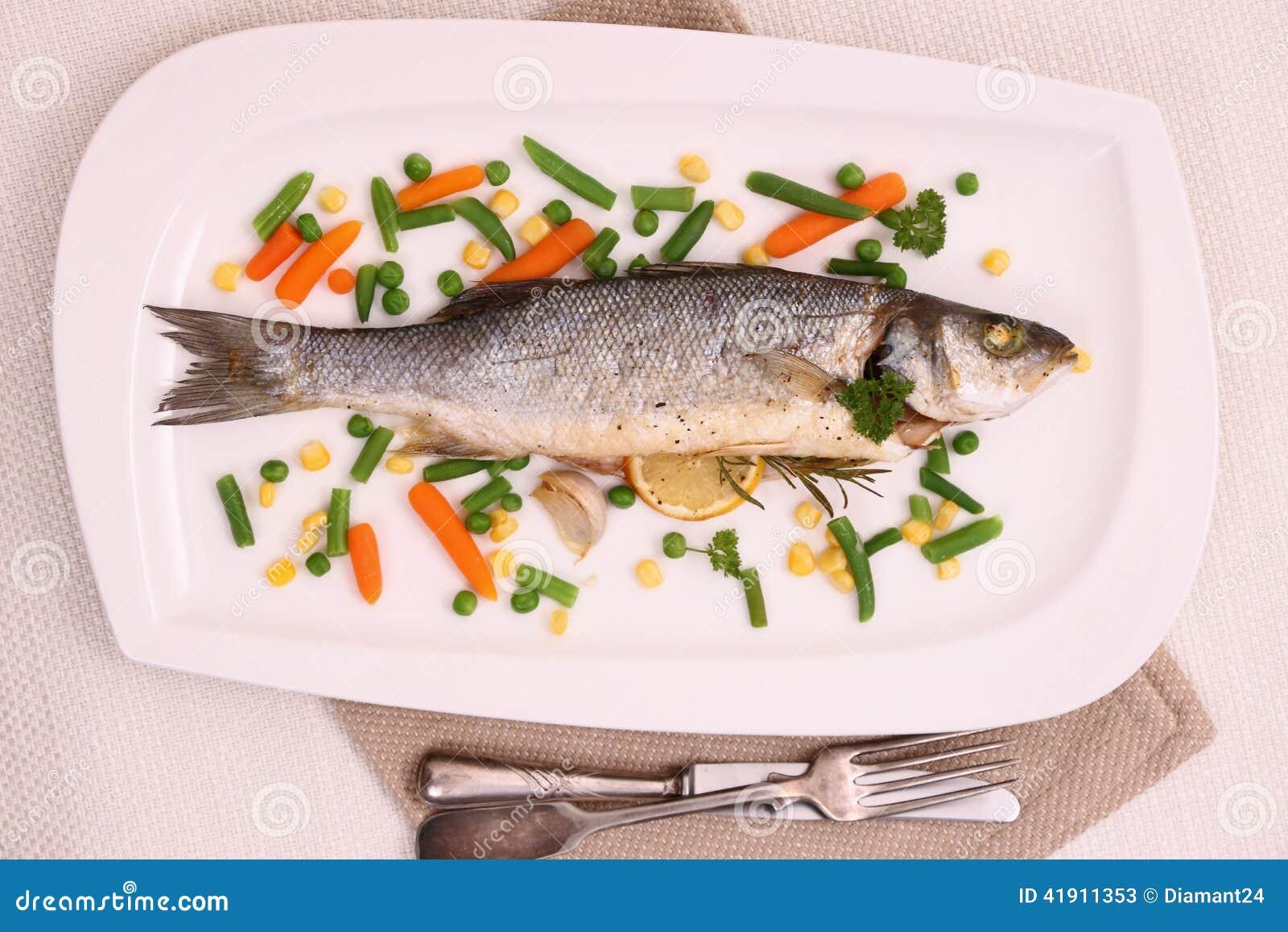 Lubina entera frita con las verduras y el limón