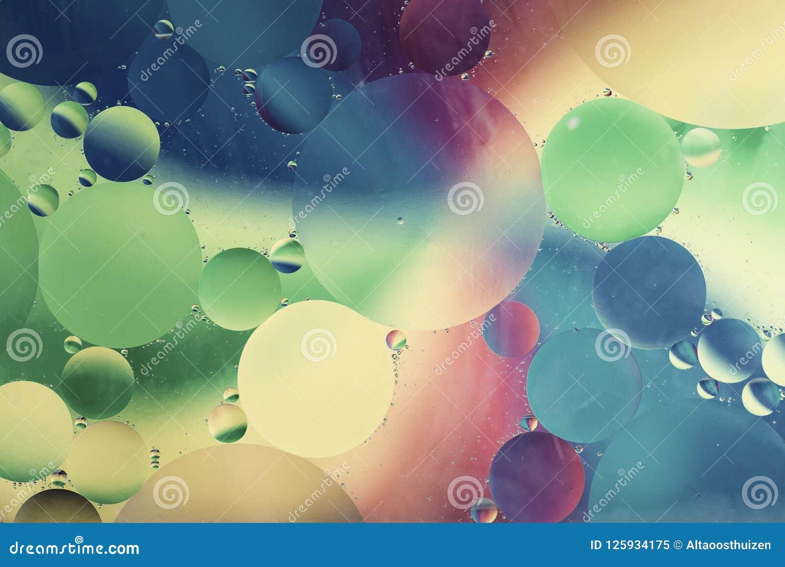 Lubrifique gotas no macro da água com um fundo colorido