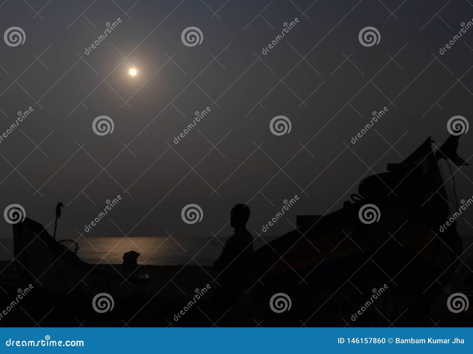 Luce di luna alla spiaggia con il pescatore e la sua ombra della barca