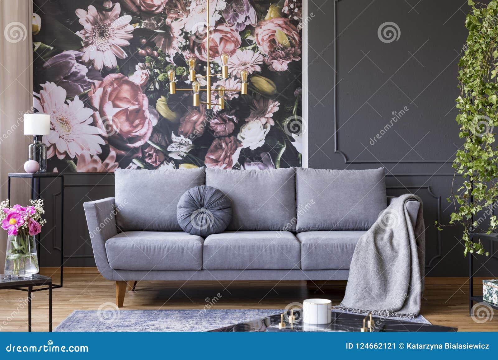 Luce dorata industriale del pendente e mobilia nera in un interno scuro del salone con la carta da parati floreale e uno strato g