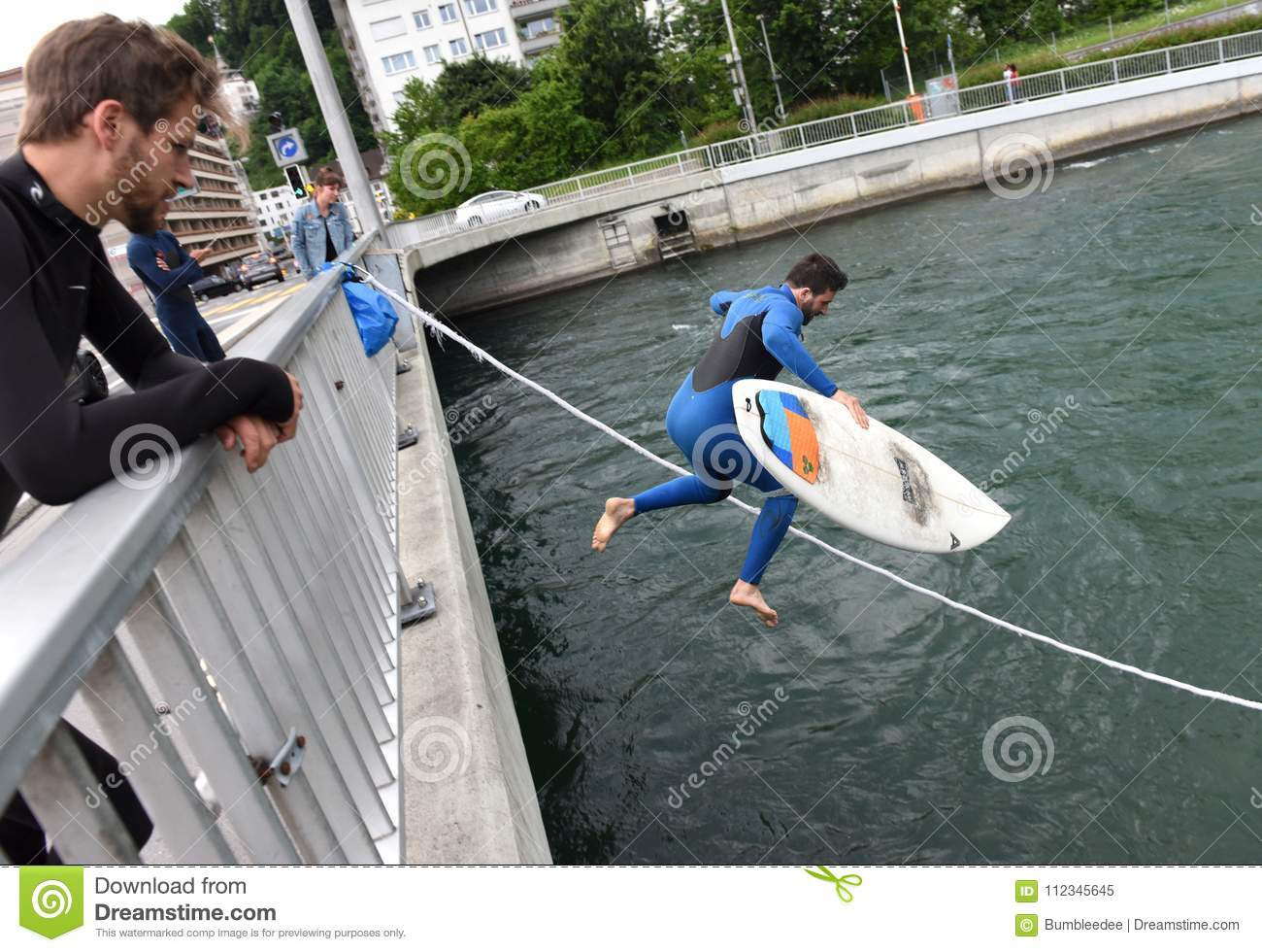 Lucerne, Switzerland - June 04, 2017: Surfer jumps from the bridge in Reuss river in Lucerne, Switzerland.
