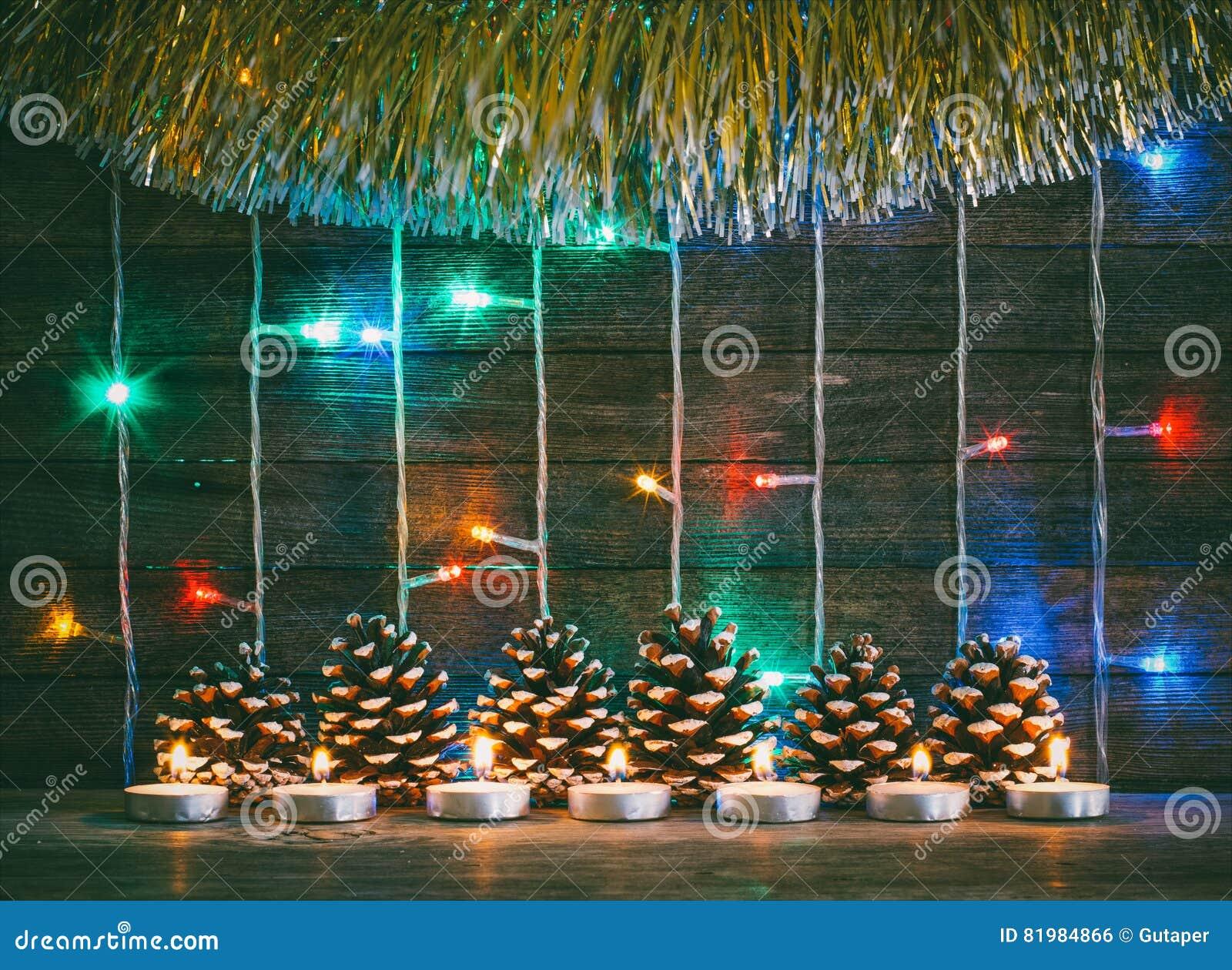 Luces coloridas de guirnaldas, de conos de abeto y de velas en el fondo de los viejos tableros del granero