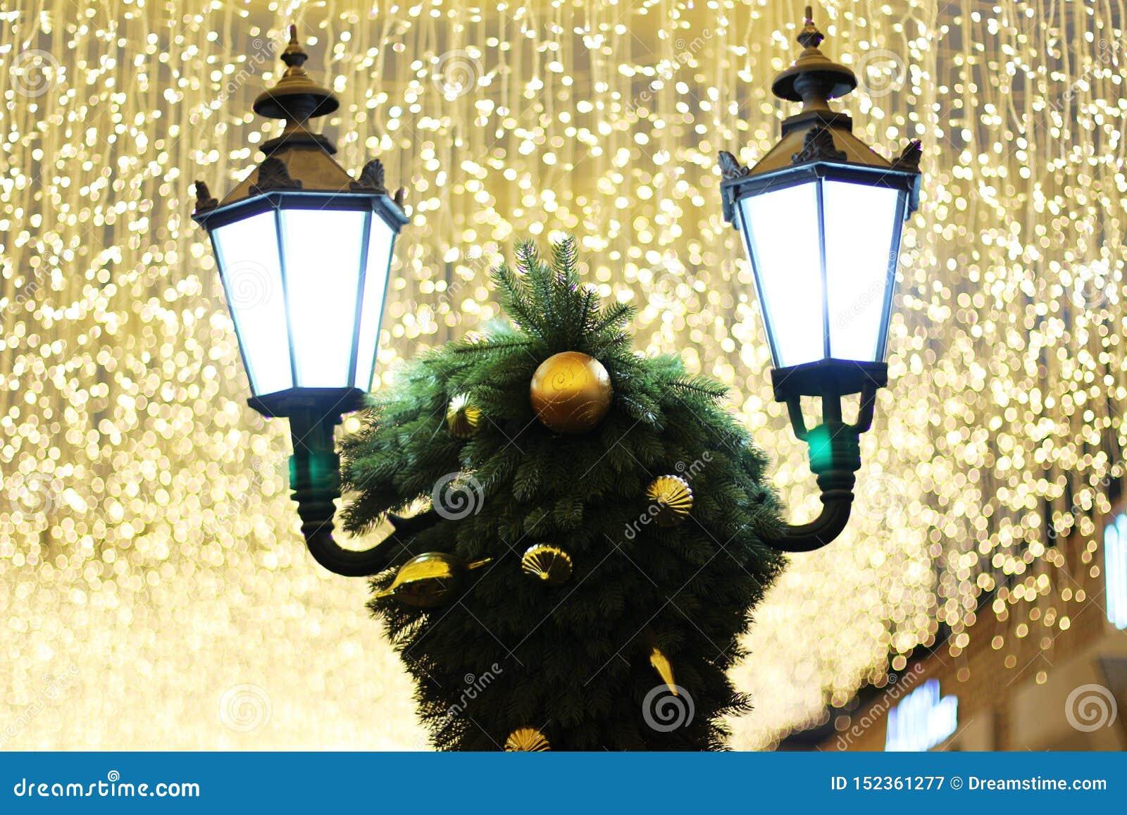 Luces de calle y decoraciones de la Navidad bajo luces brillantes