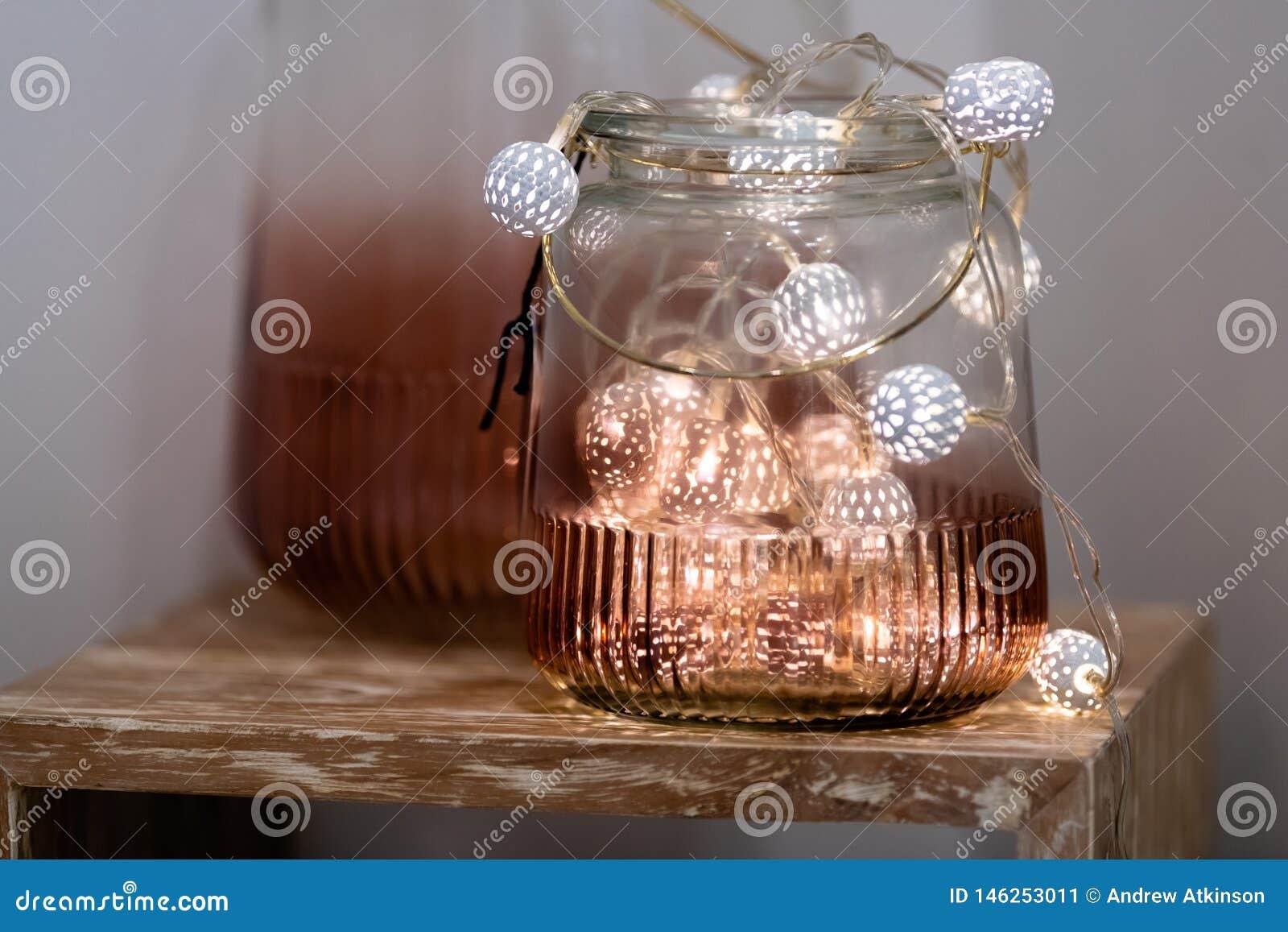 Luces de hadas blancas y rosadas del té en tarro de cristal coloreado con el fondo borroso