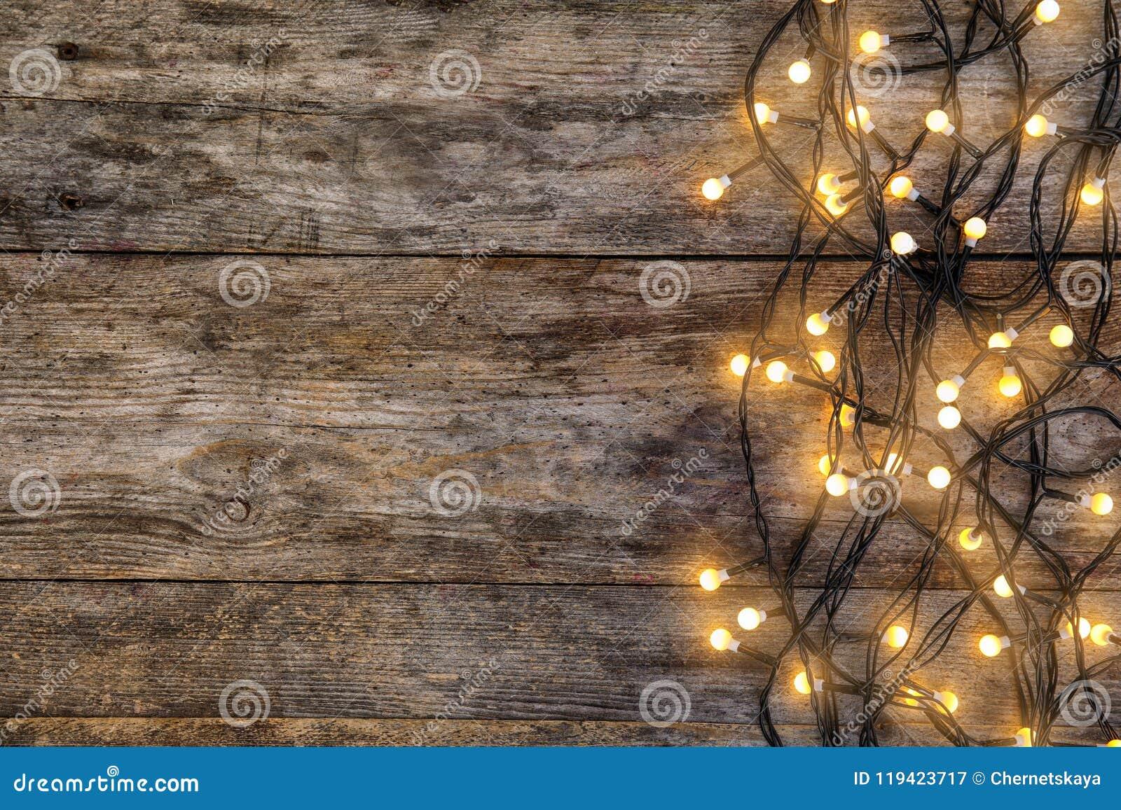 Luces de la Navidad que brillan intensamente en fondo de madera