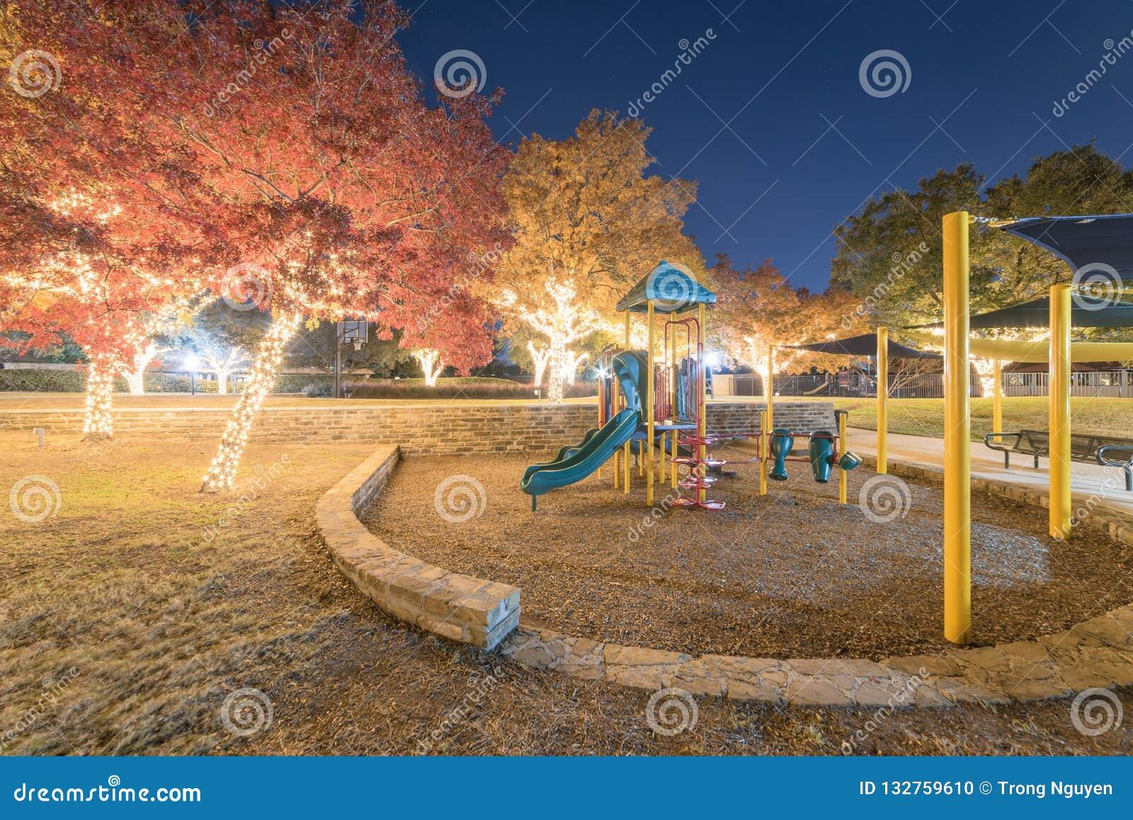 Luces y follaje de otoño al aire libre coloridos del árbol del día de fiesta en el público