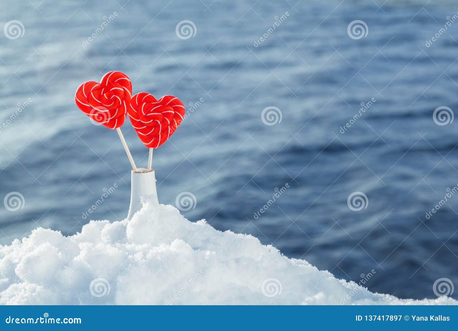 Lucettes de coeurs dans la neige sur le fond des vagues de mer Date romantique, déclaration de l amour, Saint-Valentin