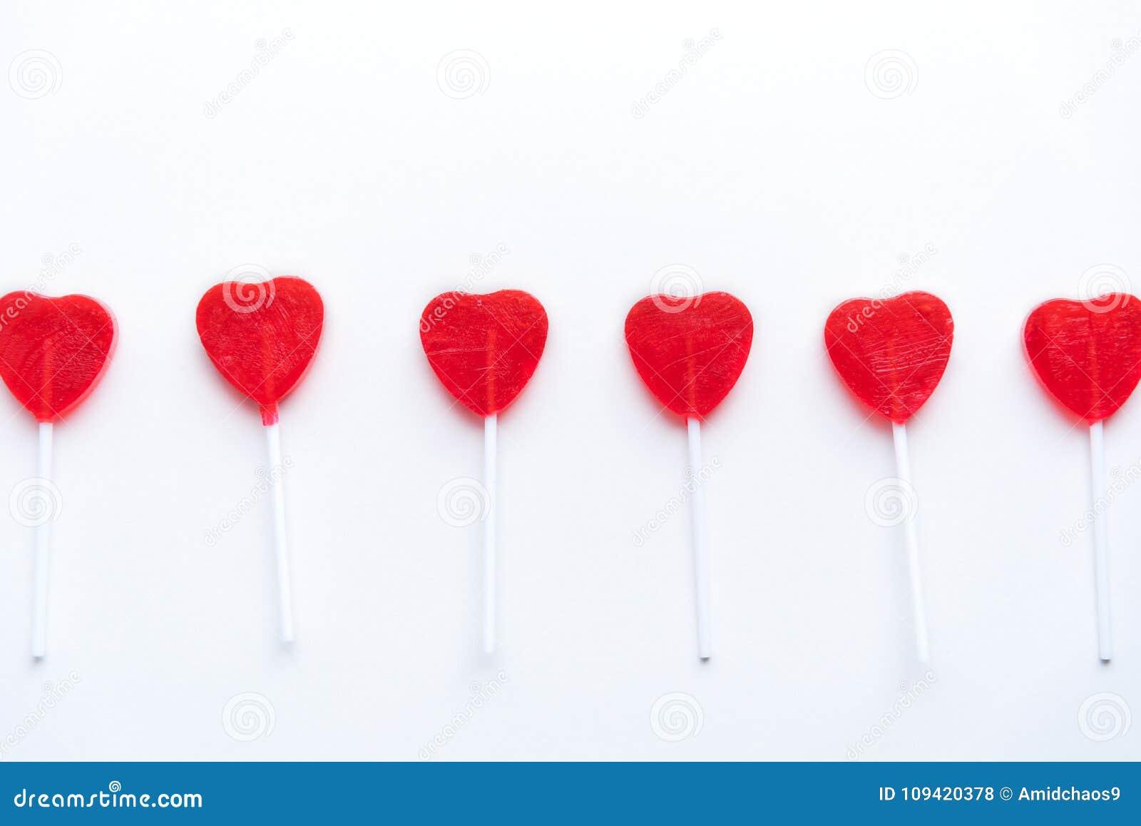 Lucettes rouges de coeur de Valentine dans une rangée à travers le fond blanc