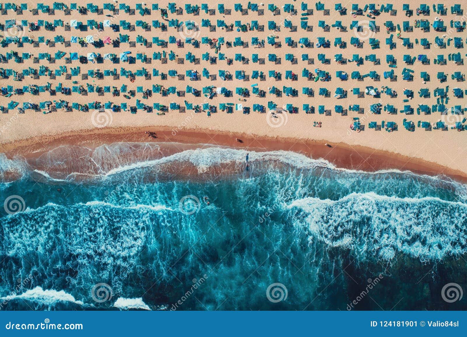 Lucht hoogste mening over het strand Paraplu s, zand en overzeese golven