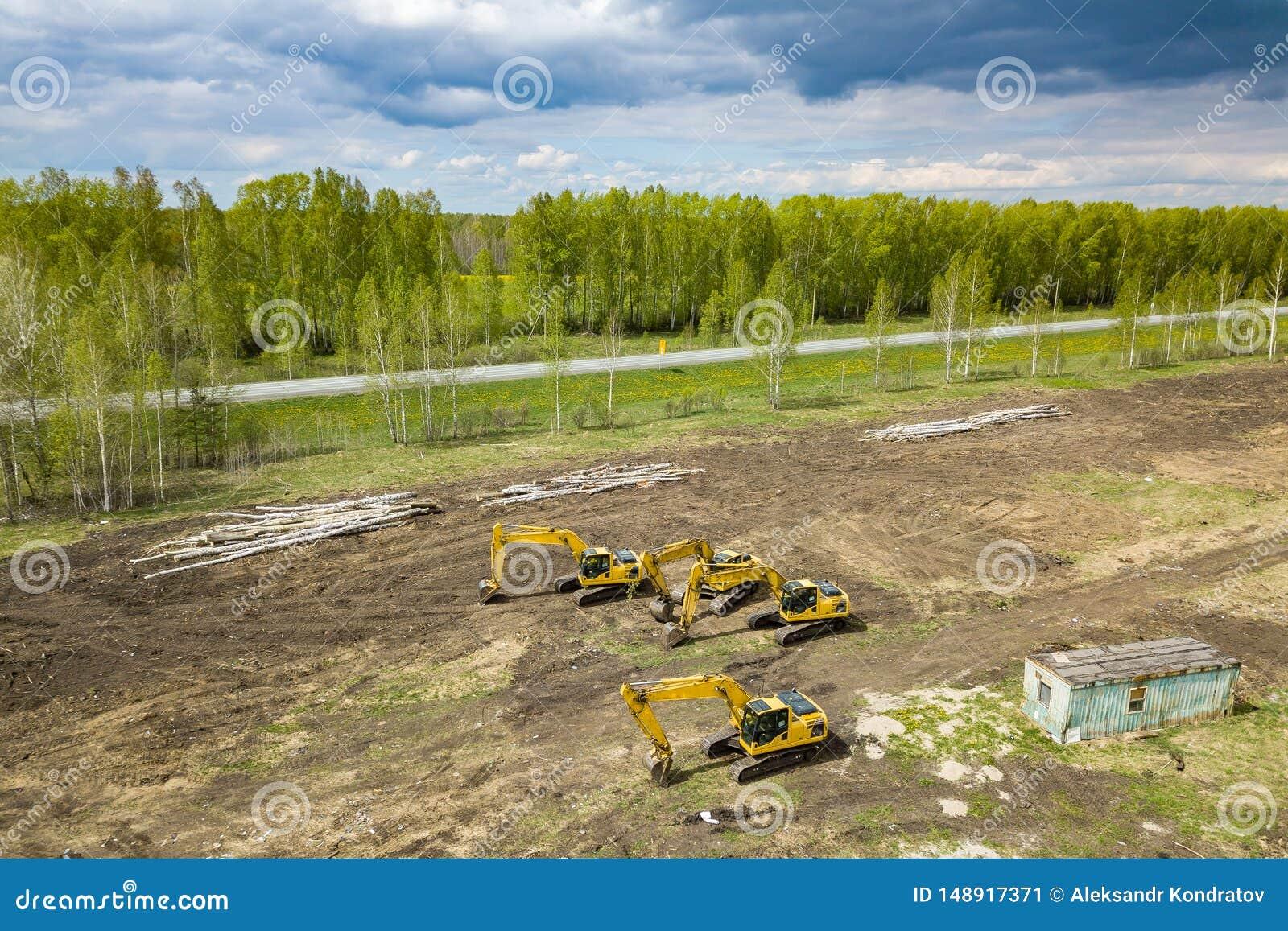 Lucht hoogste mening van vier gele kruippakjegraafwerktuigen die zich op grond dichtbij de bouwwerf bevinden en graven wachten te