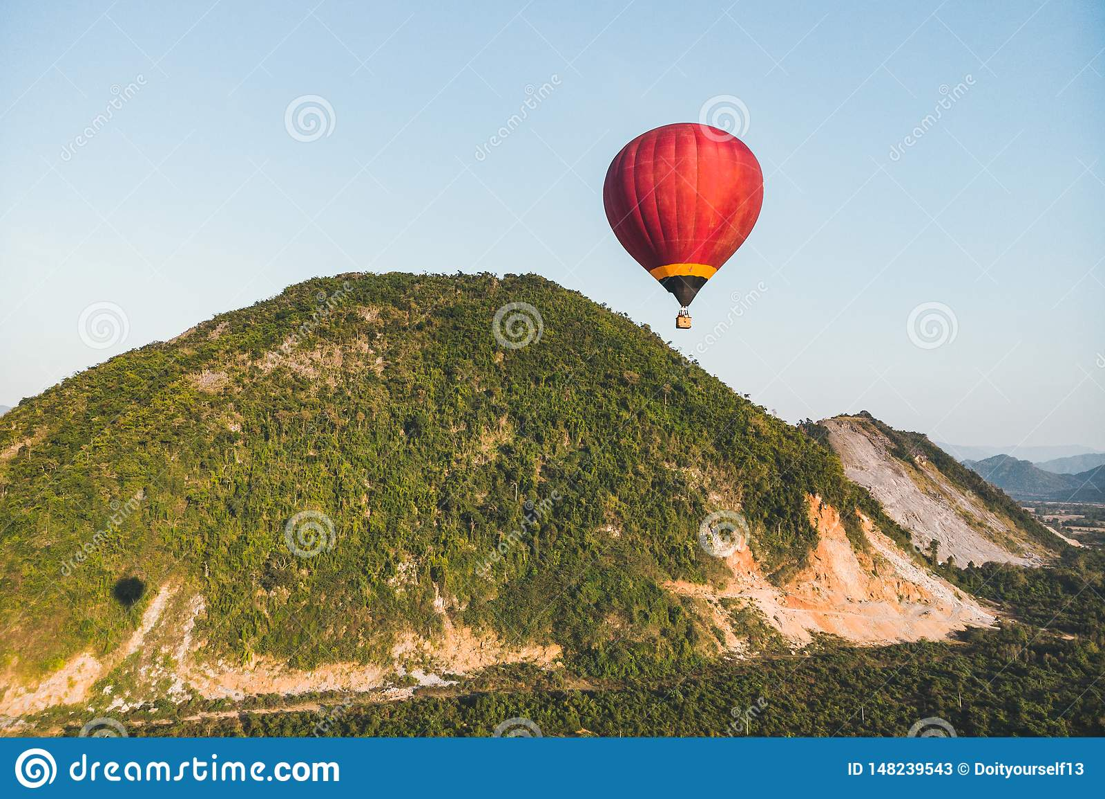 Luchtballonnen die over berg en groen padieveld in Vang Vieng, Laos vliegen