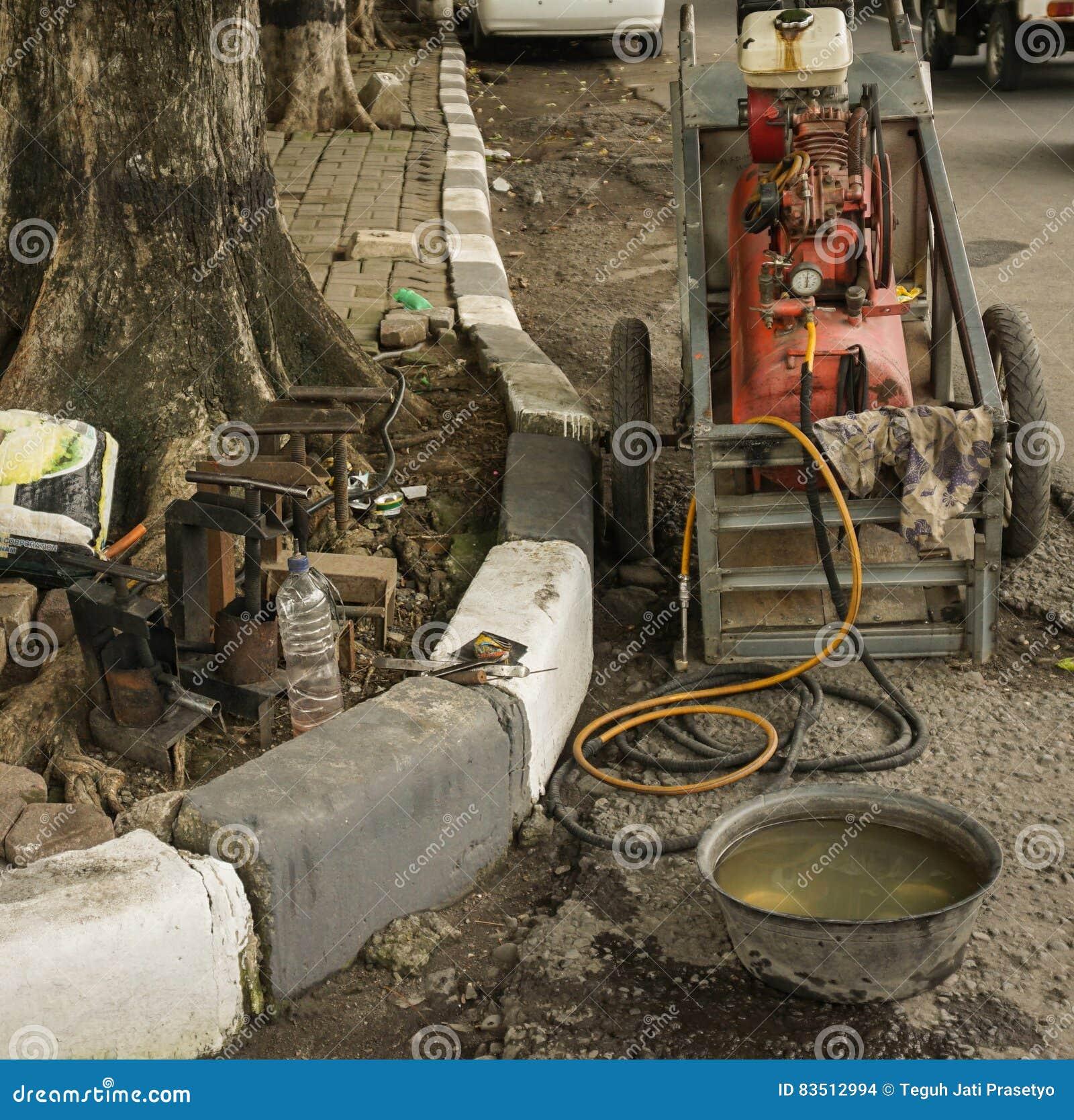 Luchtcompressor en water die gewoonlijk wordt om een bandfoto te herstellen in Semarang Indonesië wordt genomen gebruikt dat