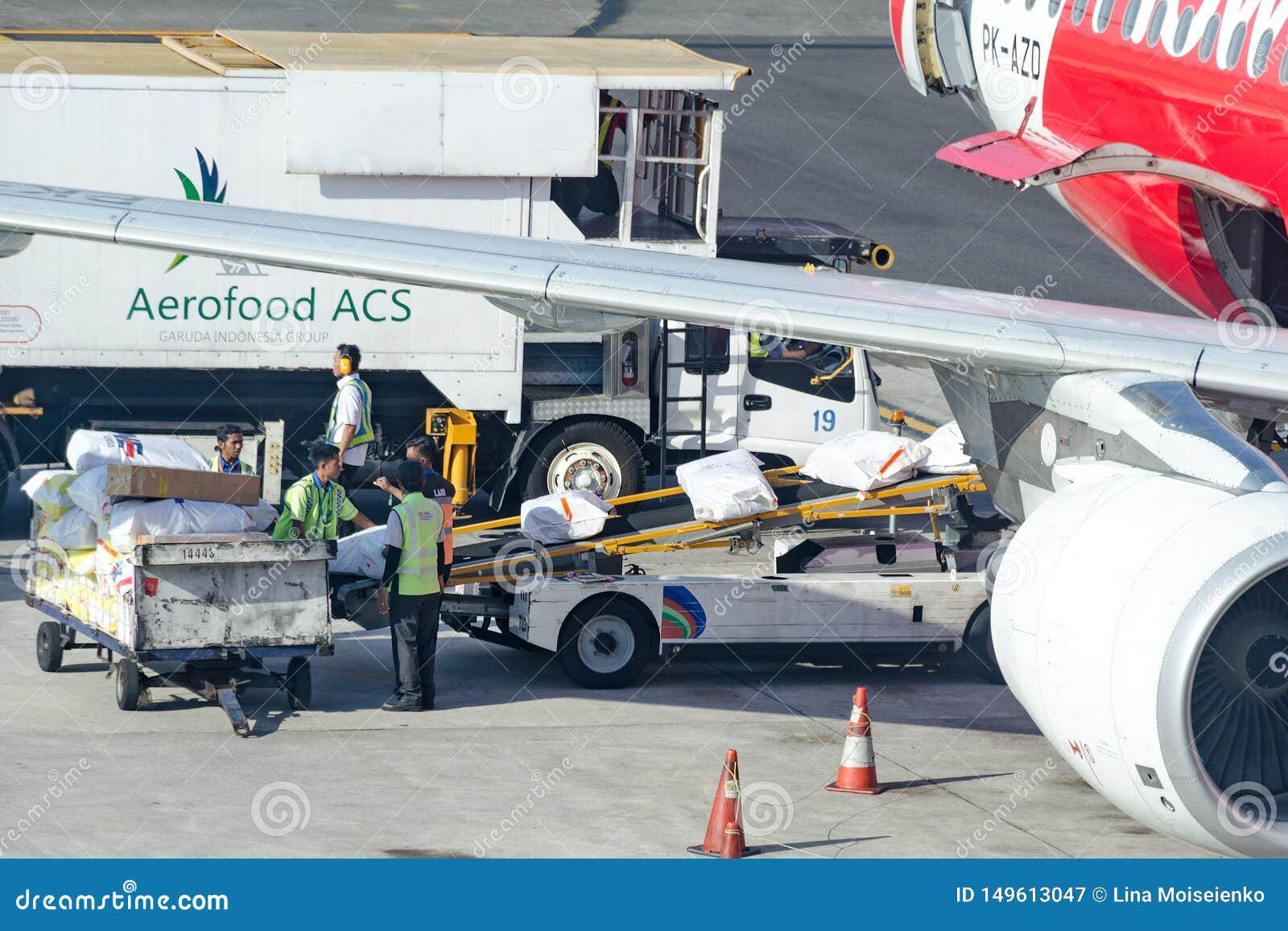 Luchthavenarbeiders die cateringslevering laden in vliegtuigen