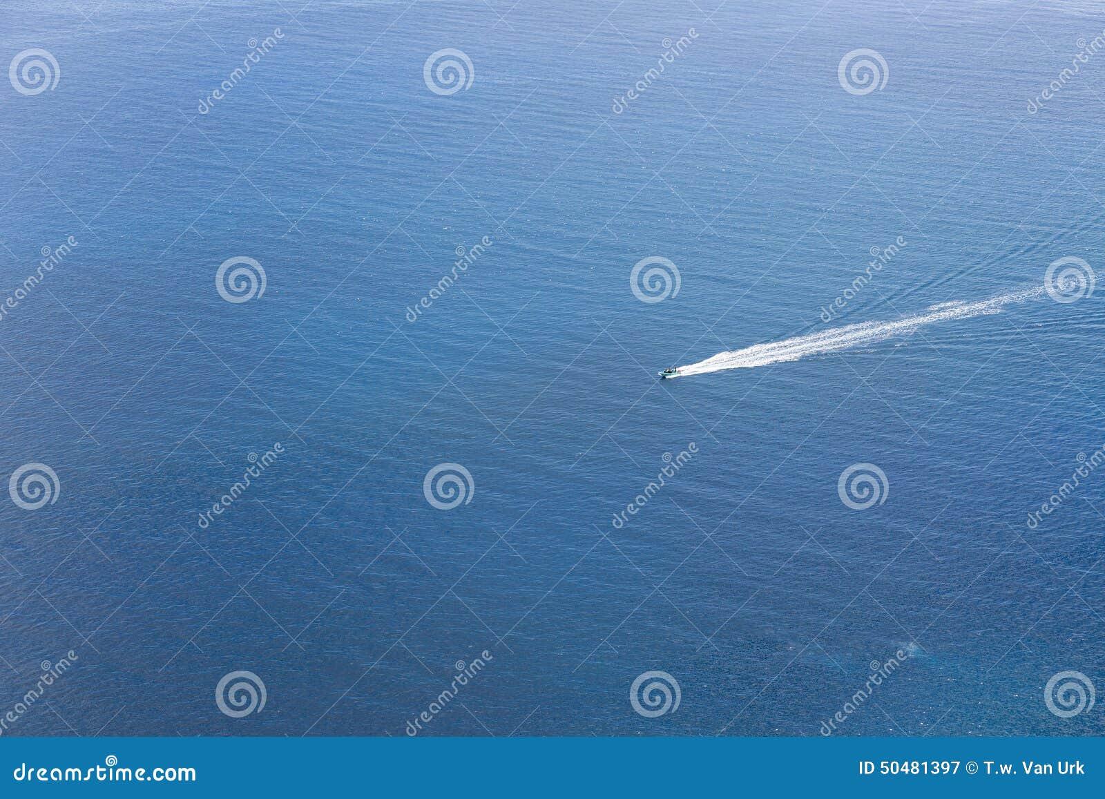 Luchtmening van een klein schip die bij een blauwe oceaan navigeren