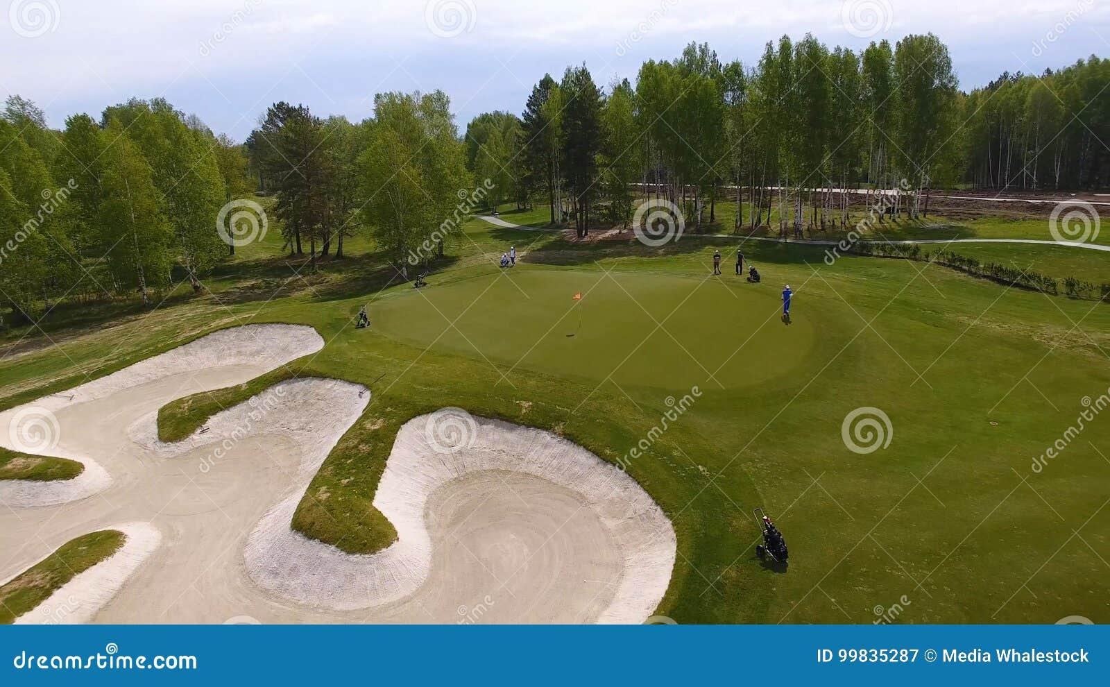 Luchtmening van golfspelers die bij groen zetten spelen Professionele spelers op een groene golfcursus