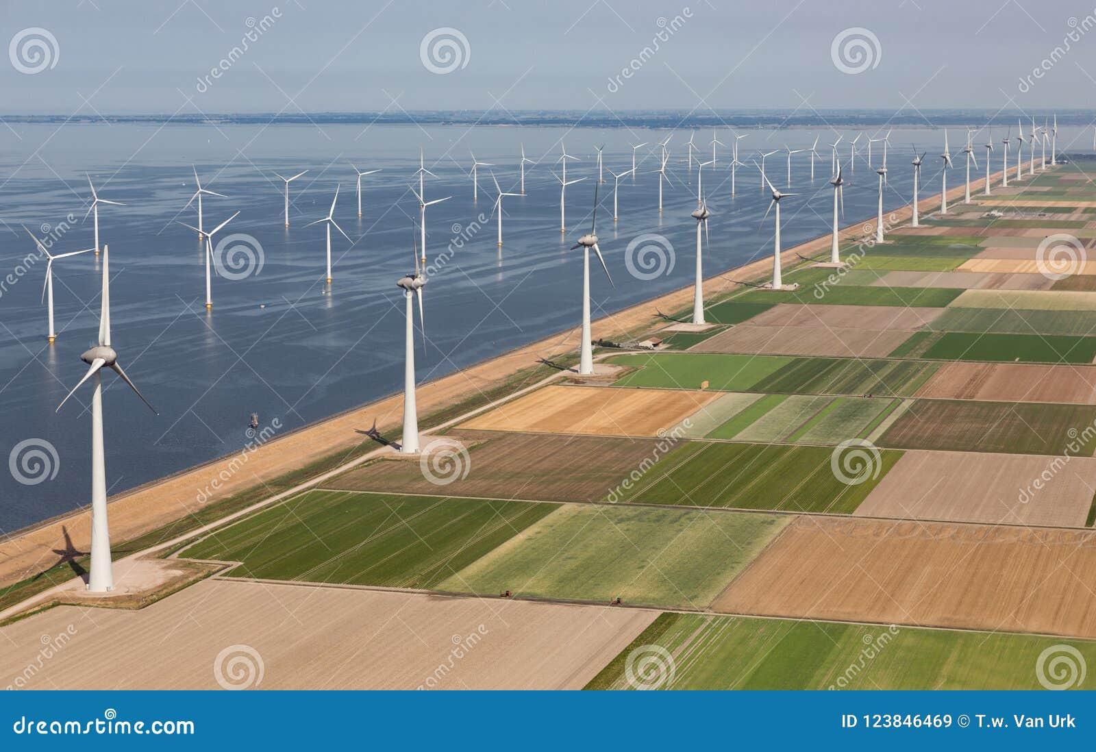 Luchtmenings Nederlands landschap met zeewindturbines langs kust
