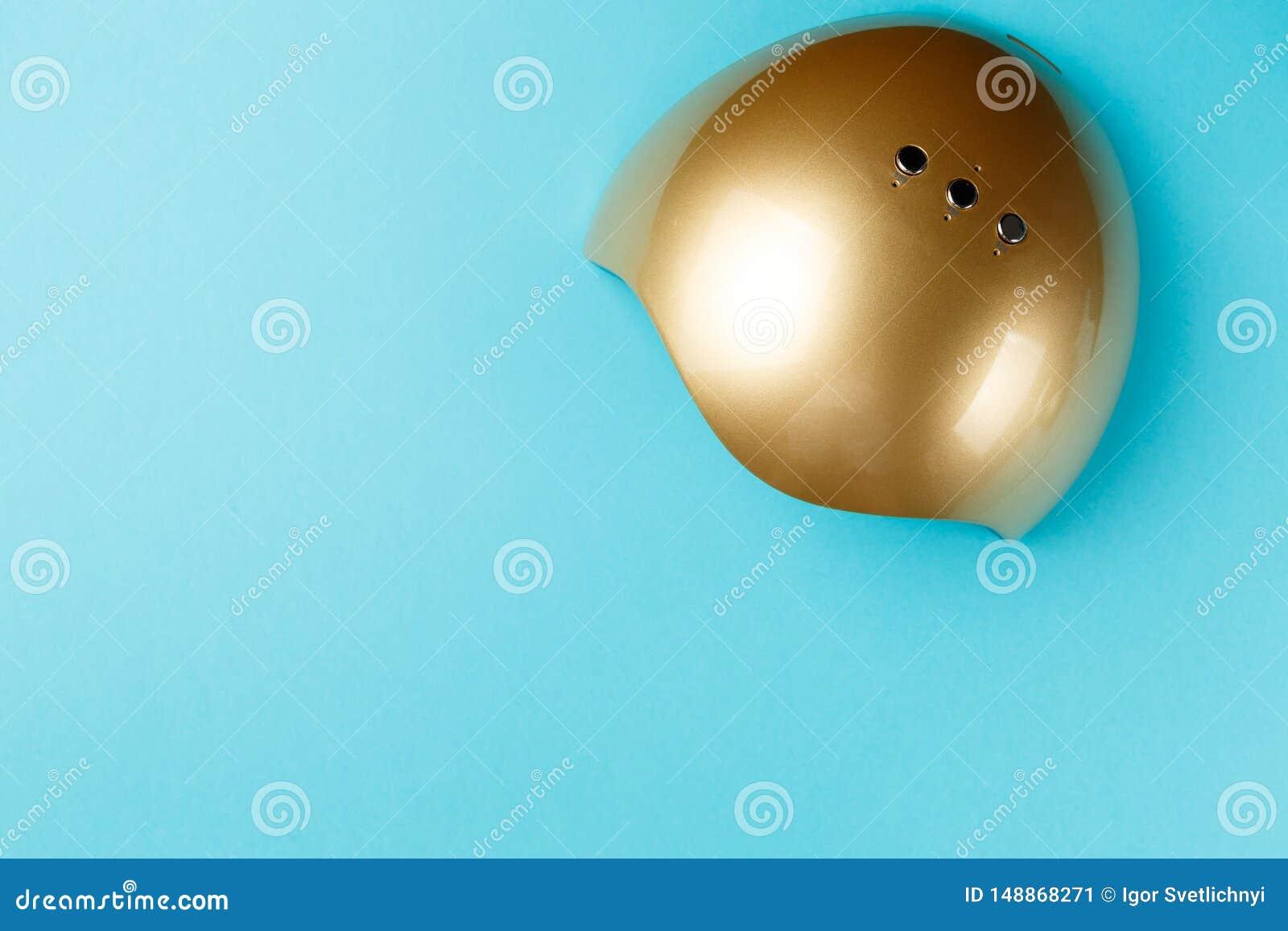 Luci UV della lampada per i chiodi su fondo blu Vista superiore Disposizione piana Copi lo spazio concetto creativo minimo