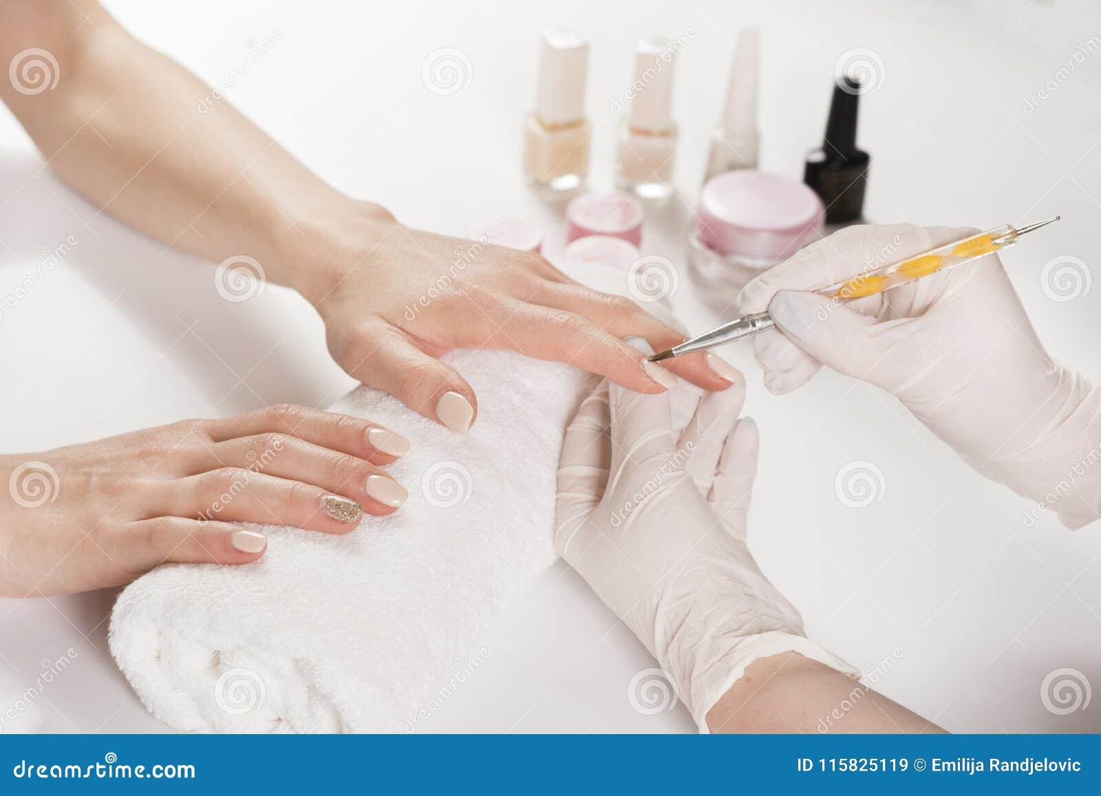 Lucidatura di unghie professionale del dito nello studio del manicure sulle mani della giovane donna