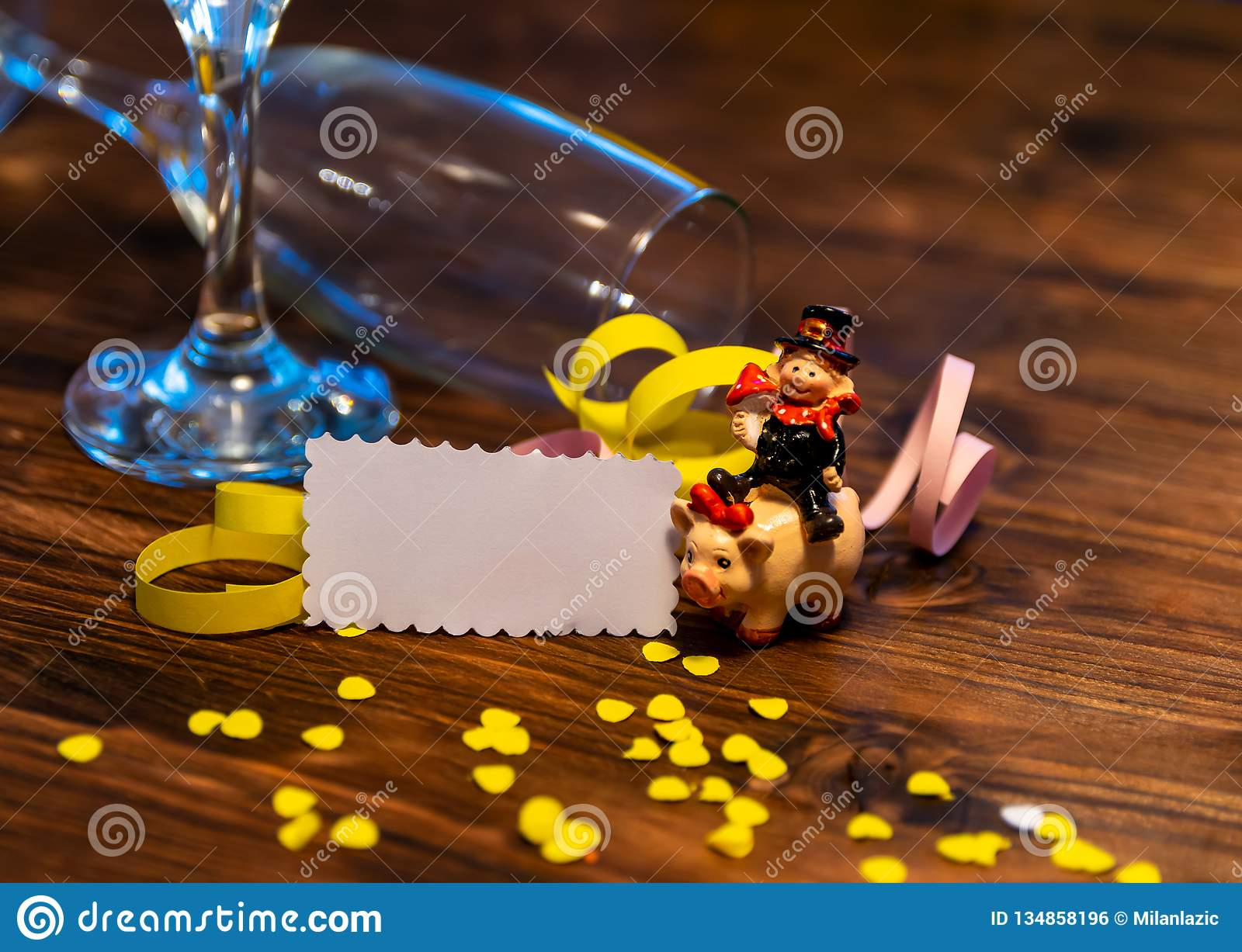 A lucky charm on New Year`s Eve. A chimney sweep on a pig with confetti, paper and champagne glasses