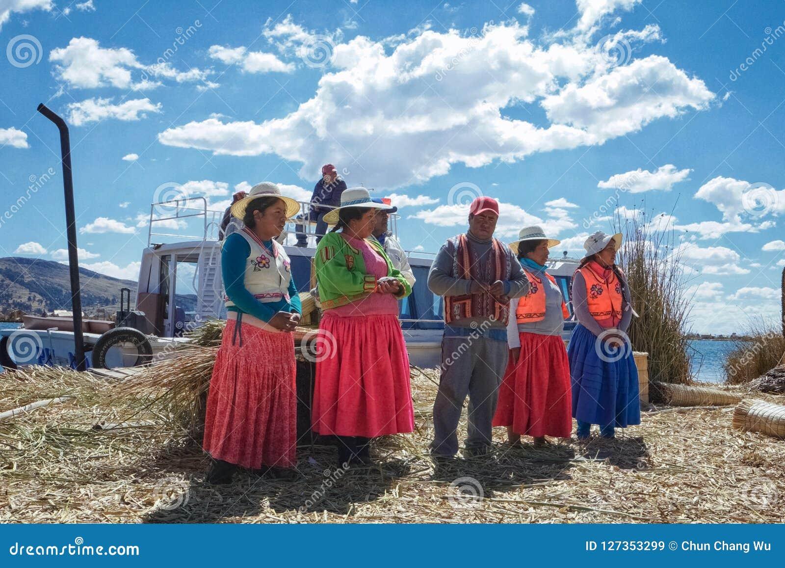 Ludzie żyje na trzcinowej wyspie Jeziorny Titicaca one przedstawiają i mówją turystom opowieści o jak one robi l