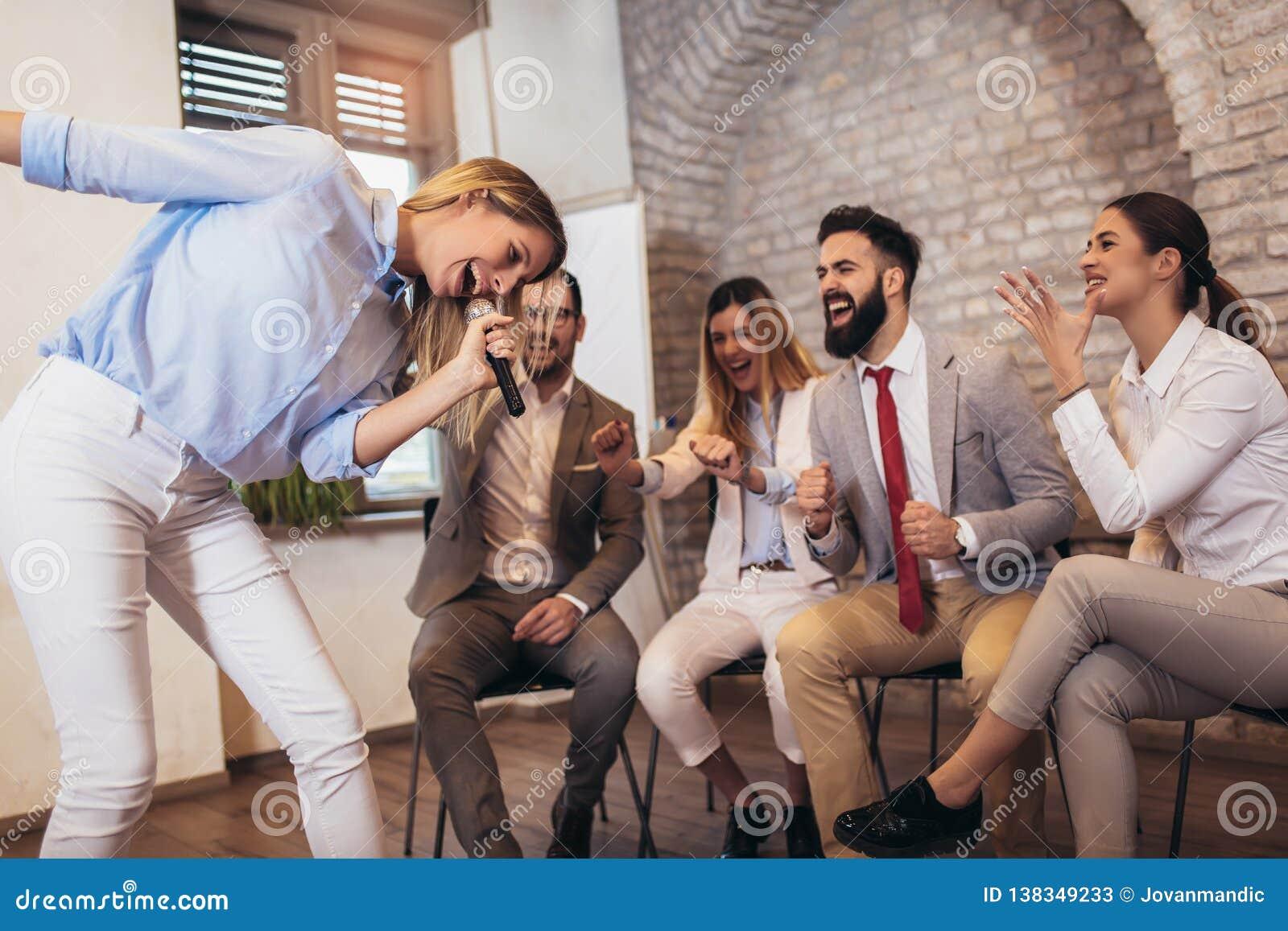 Ludzie biznesu robi drużynowemu ćwiczeniu szkoleniowemu podczas drużynowego budynku seminaryjnego śpiewackiego karaoke
