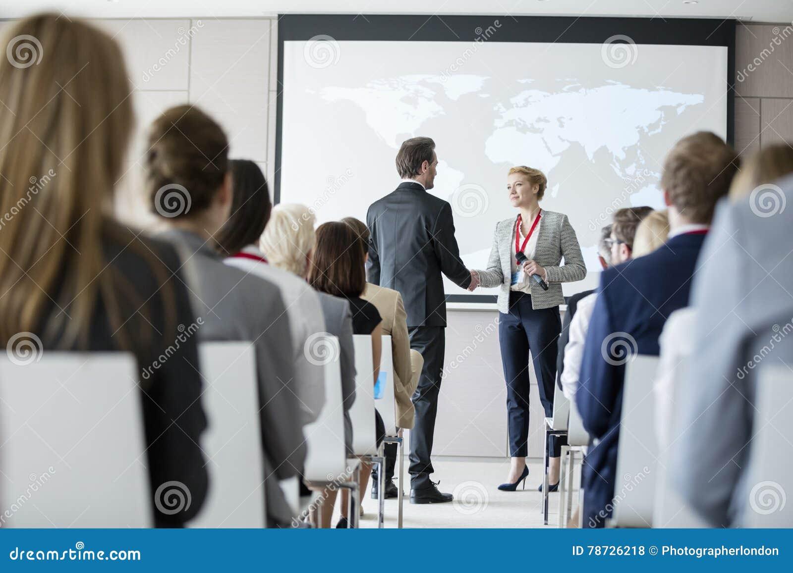 Ludzie biznesu trząść ręki podczas konwersatorium przy convention center