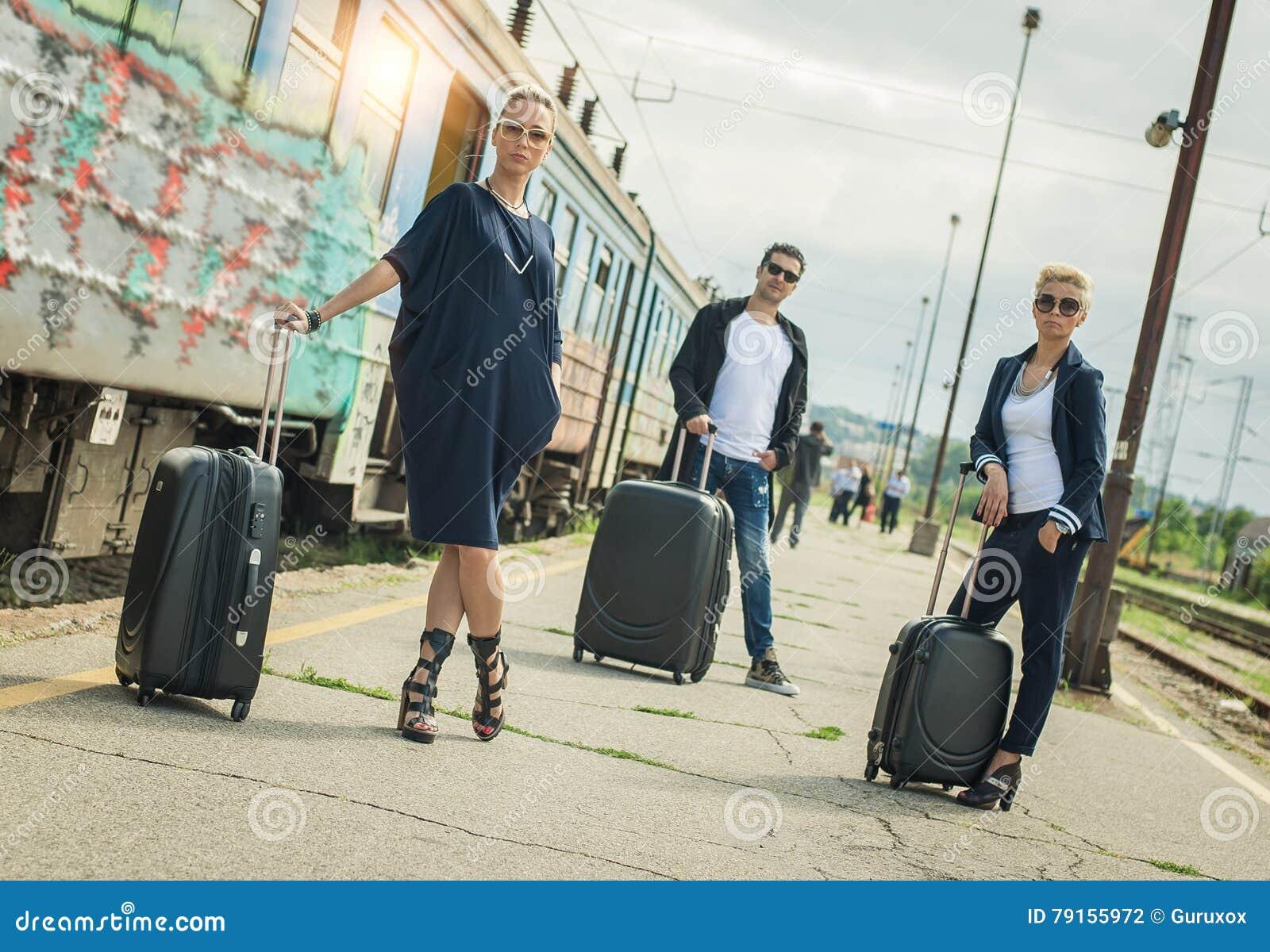 Ludzie biznesu z walizką pozuje na staci kolejowej
