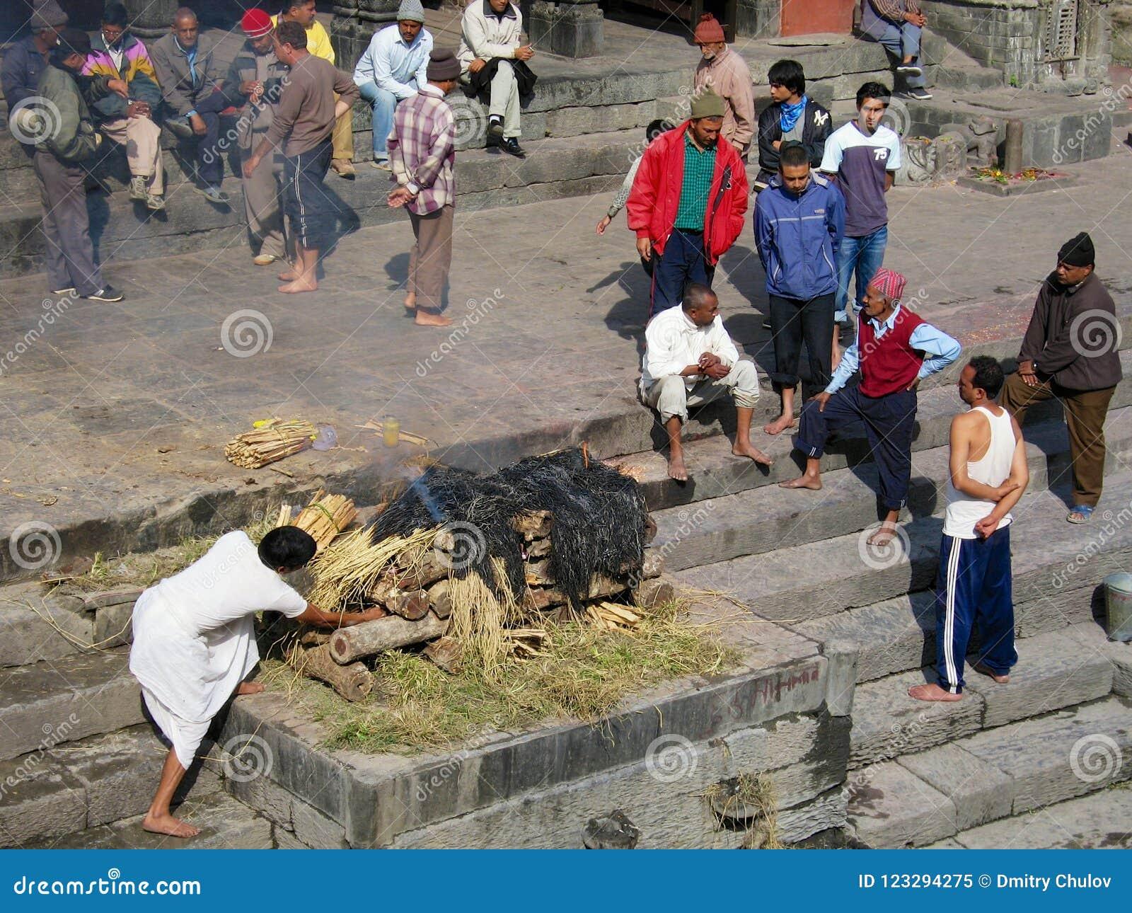 Ludzie brali udział w tradycyjnej kremaci ceremonii przy Pashupatinath świątynią na Bagmati brzeg rzeki w Kathmandu, Nepal