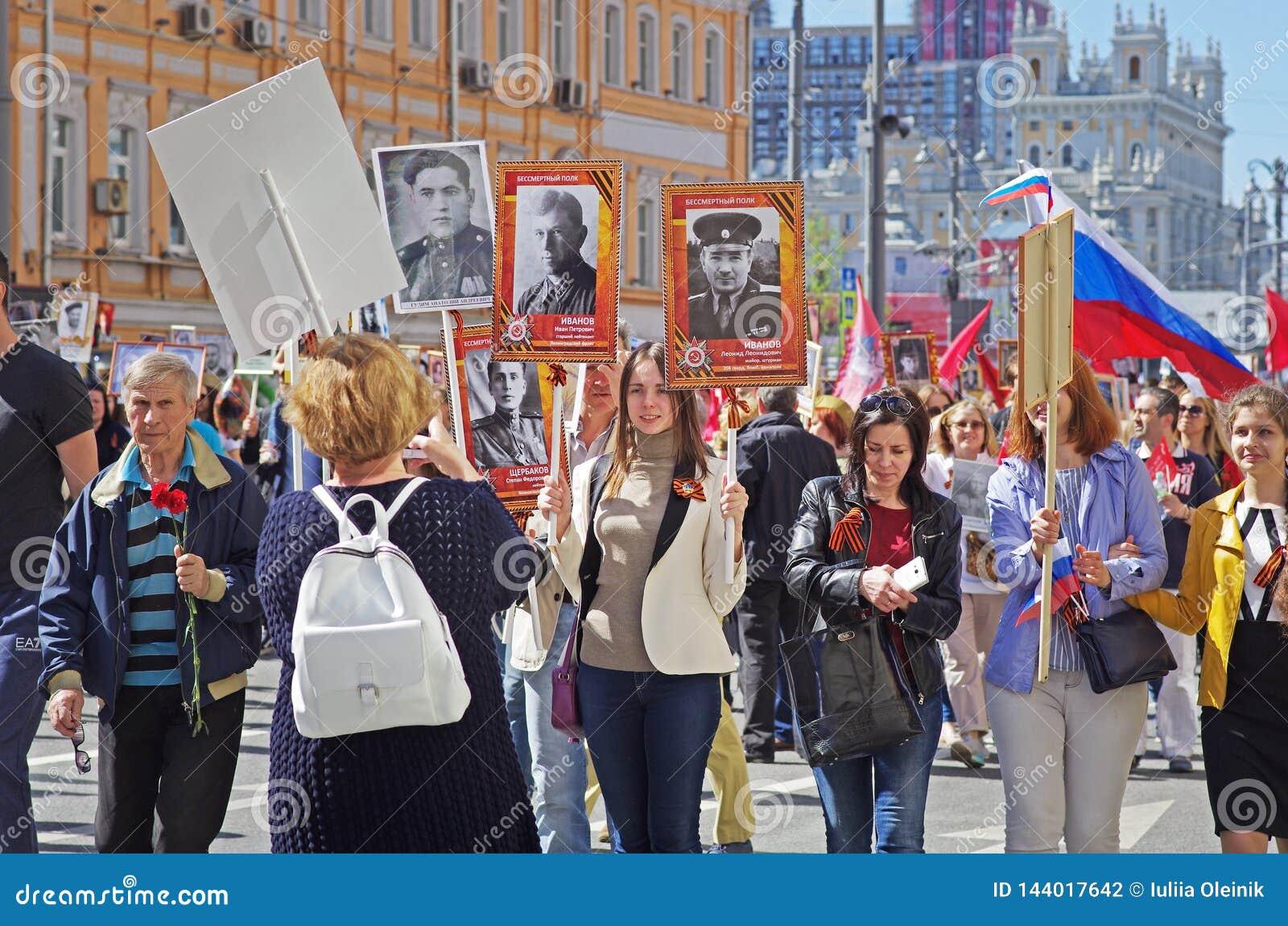 Ludzie chwytów portretów ich krewni w akcji «Nieśmiertelny pułk «na zwycięstwo dniu w Moskwa