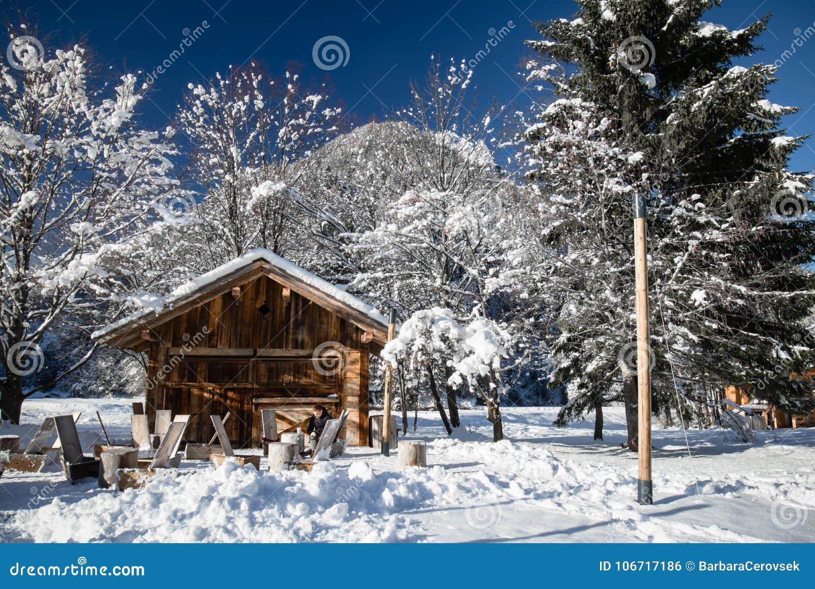 Ludzie cieszy się sunbathing w śnieżnej zimy scenerii ` s plenerowym drewnianym restauracyjnym tarasie