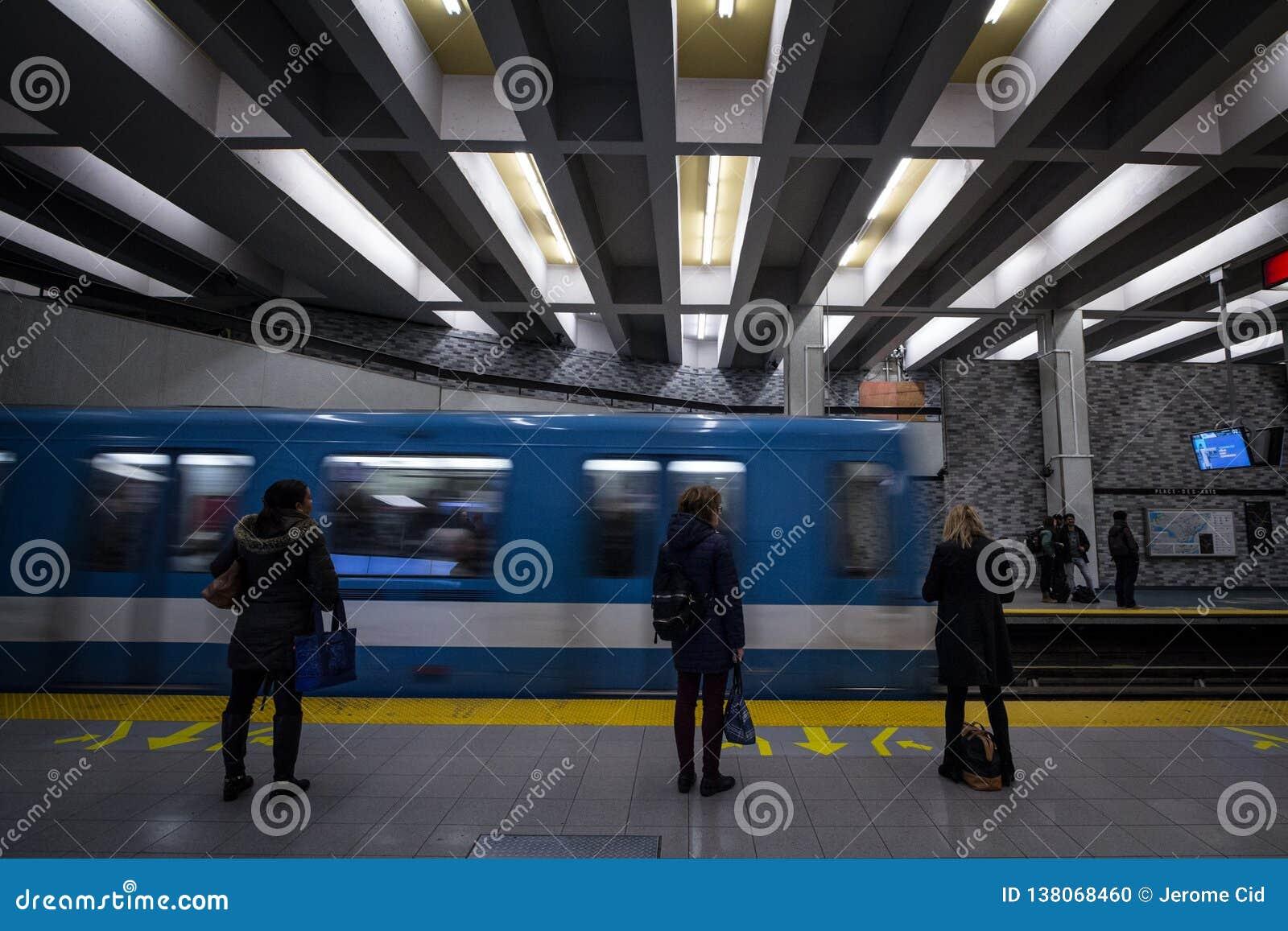 Ludzie czekać na metro w Berri-UQAM stacji platformie, zielona lina, podczas gdy metro pociąg przychodzi