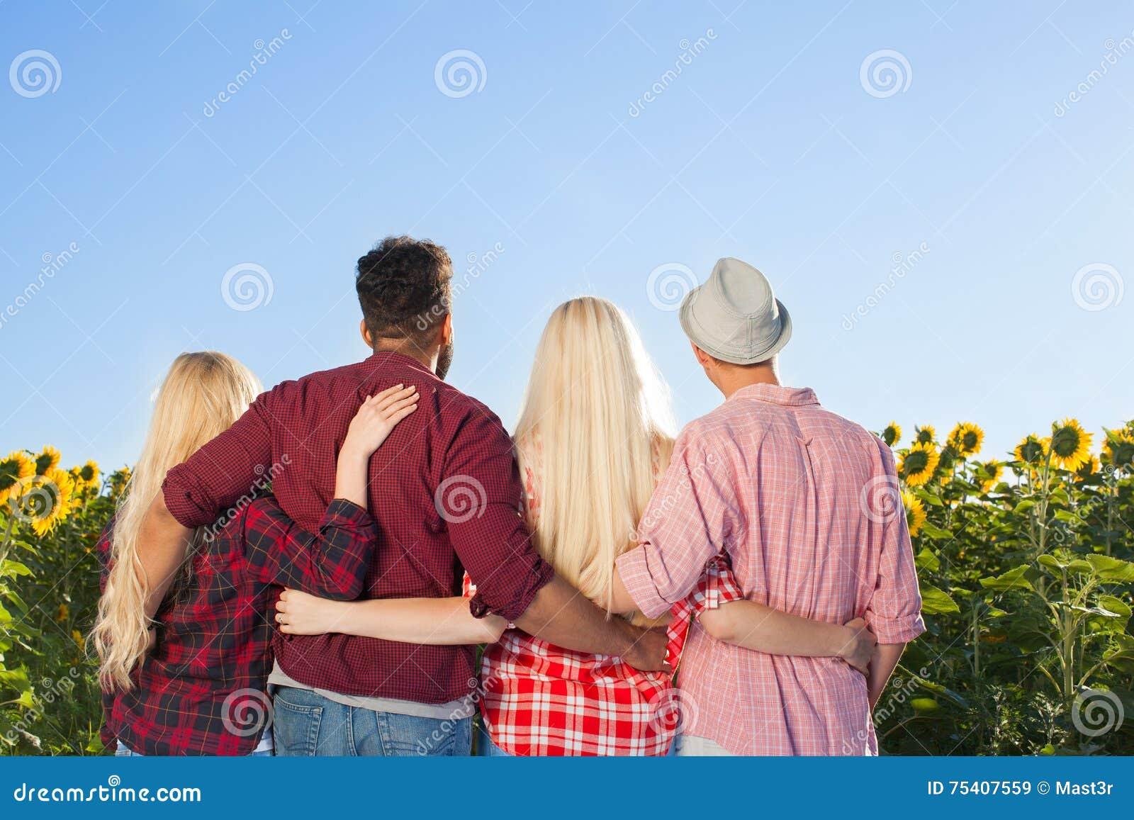 Ludzie grupują plenerowych wieś słoneczników niebieskiego nieba tyły plecy śródpolnego widok