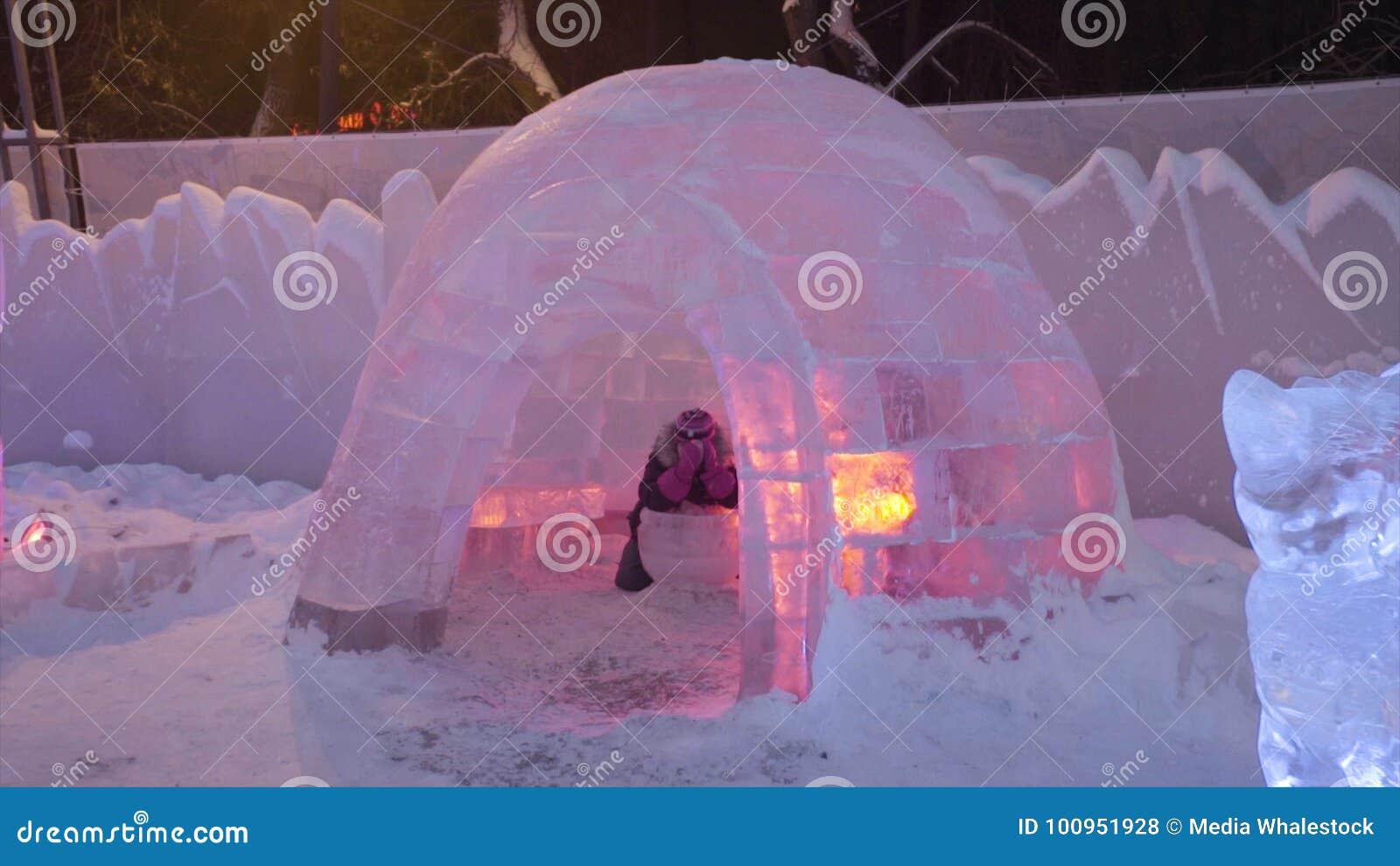 Ludzie i dziecko Chodzą W Lodowym miasteczku Podczas opadu śniegu Dziecko sztuki przy igloo w Lodowym miasteczku, śnieżna wioska