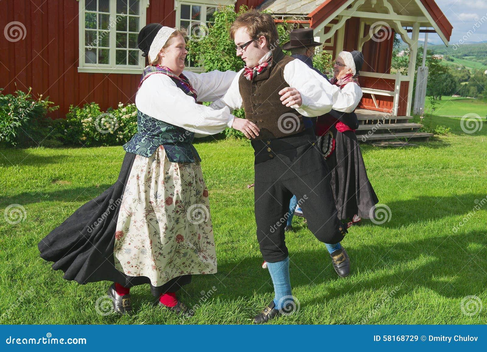 Ludzie jest ubranym dziejowych kostiumy wykonują tradycyjnego tana w Roli, Norwegia