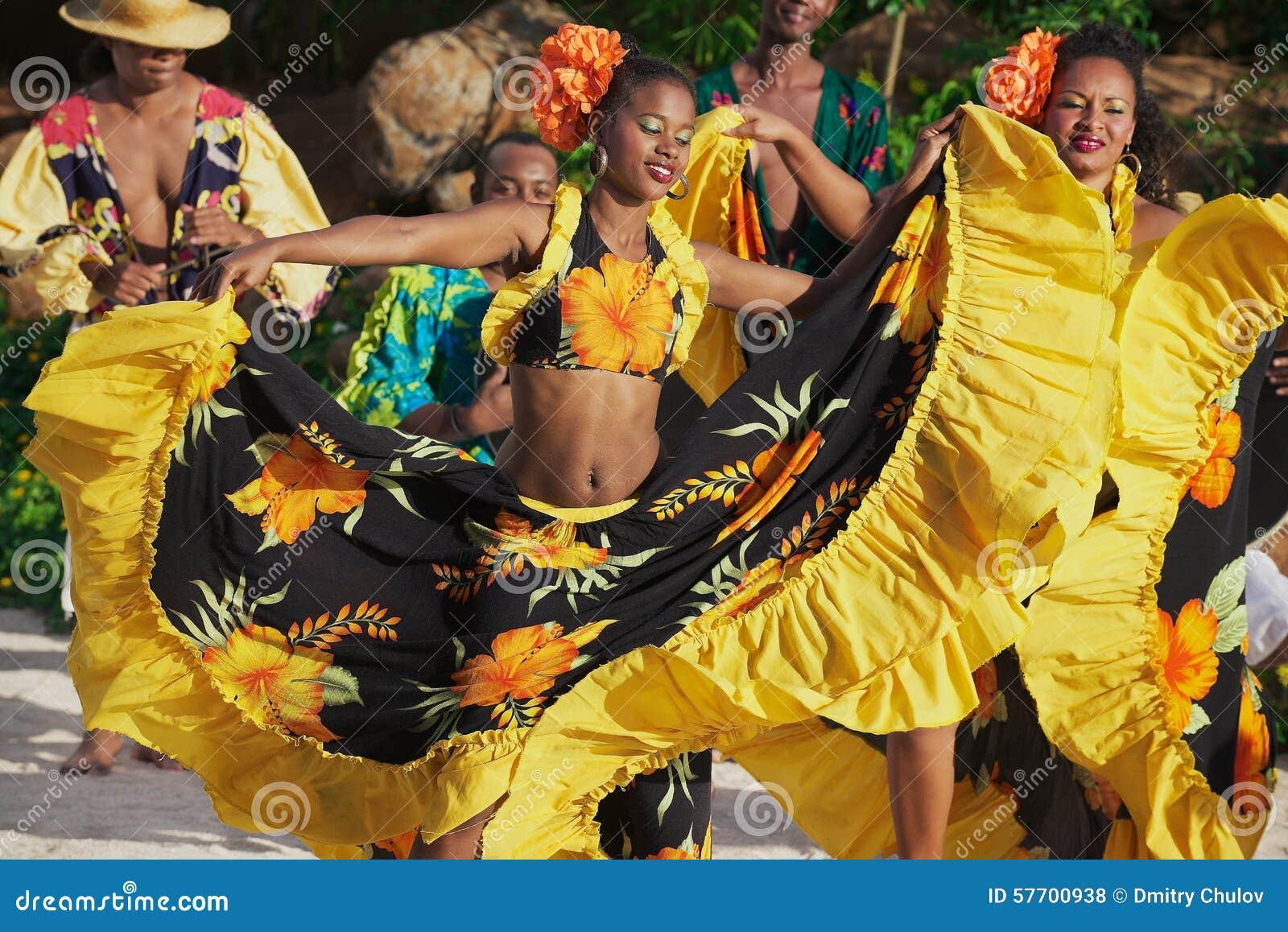 Ludzie jest ubranym kolorowe suknie wykonują tradycyjnego creole Sega tana przy zmierzchem w Ville Valio, Mauritius