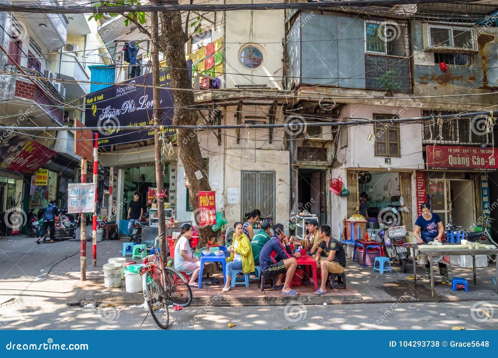 Ludzie konserwują widzią mieć ich jedzenie obok ulicy w ranku przy Hanoi, Wietnam