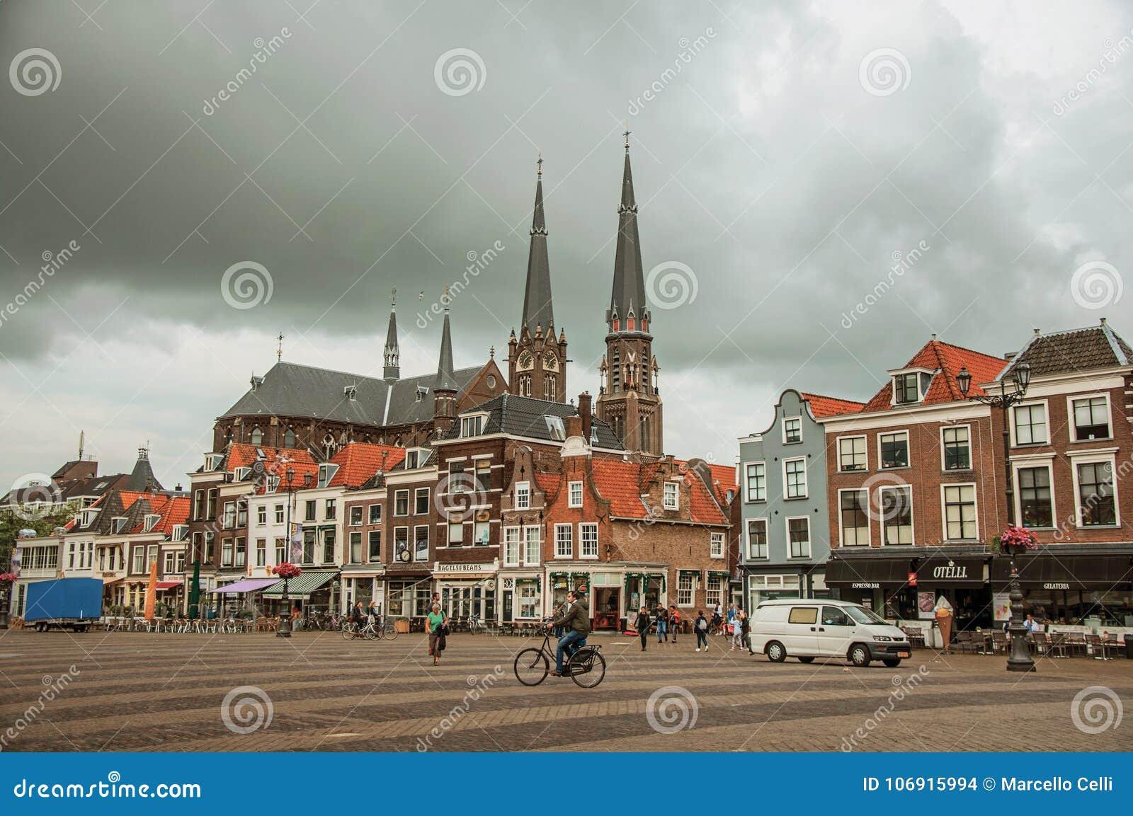 Ludzie na Targowym kwadracie, ceglanych domach z sklepami i steeple na chmurnym dniu w Delft,