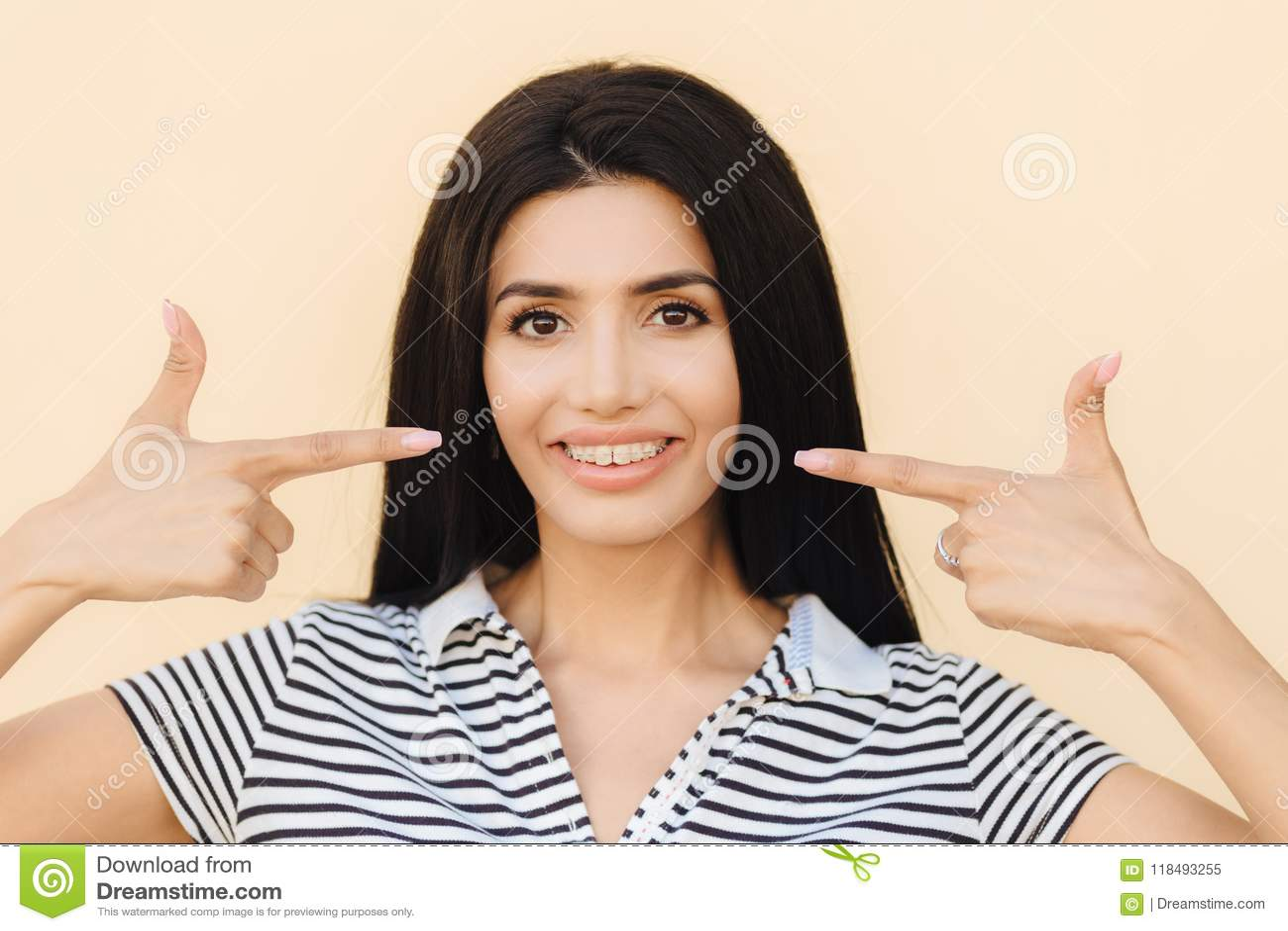 Ludzie, piękno i reklamowy pojęcie, Brunetki młoda kobieta z delikatnym uśmiechem, wskazuje przy usta z szerokim uśmiechem, brasy