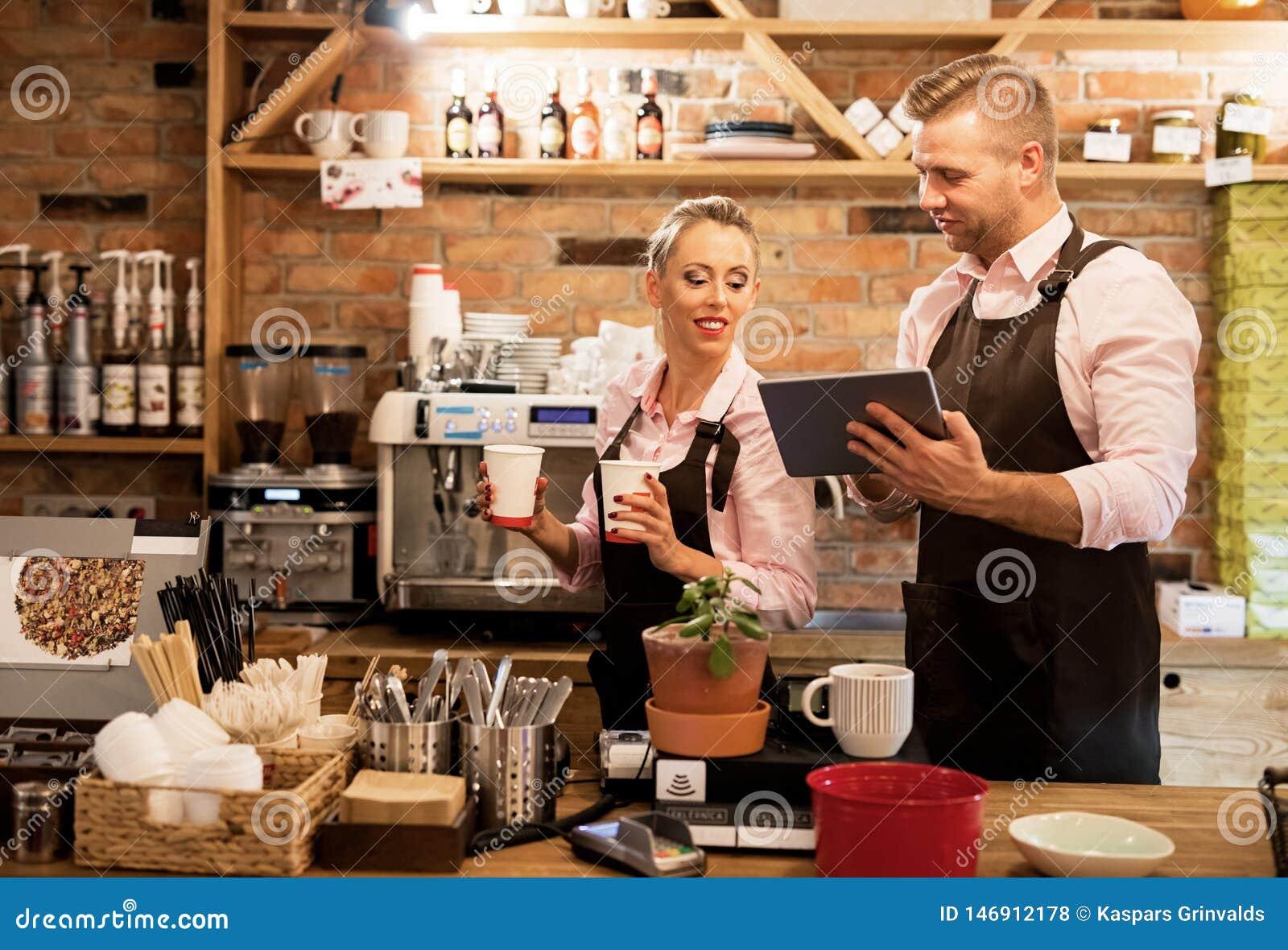 Ludzie pracuje w kawiarni i używa technikę